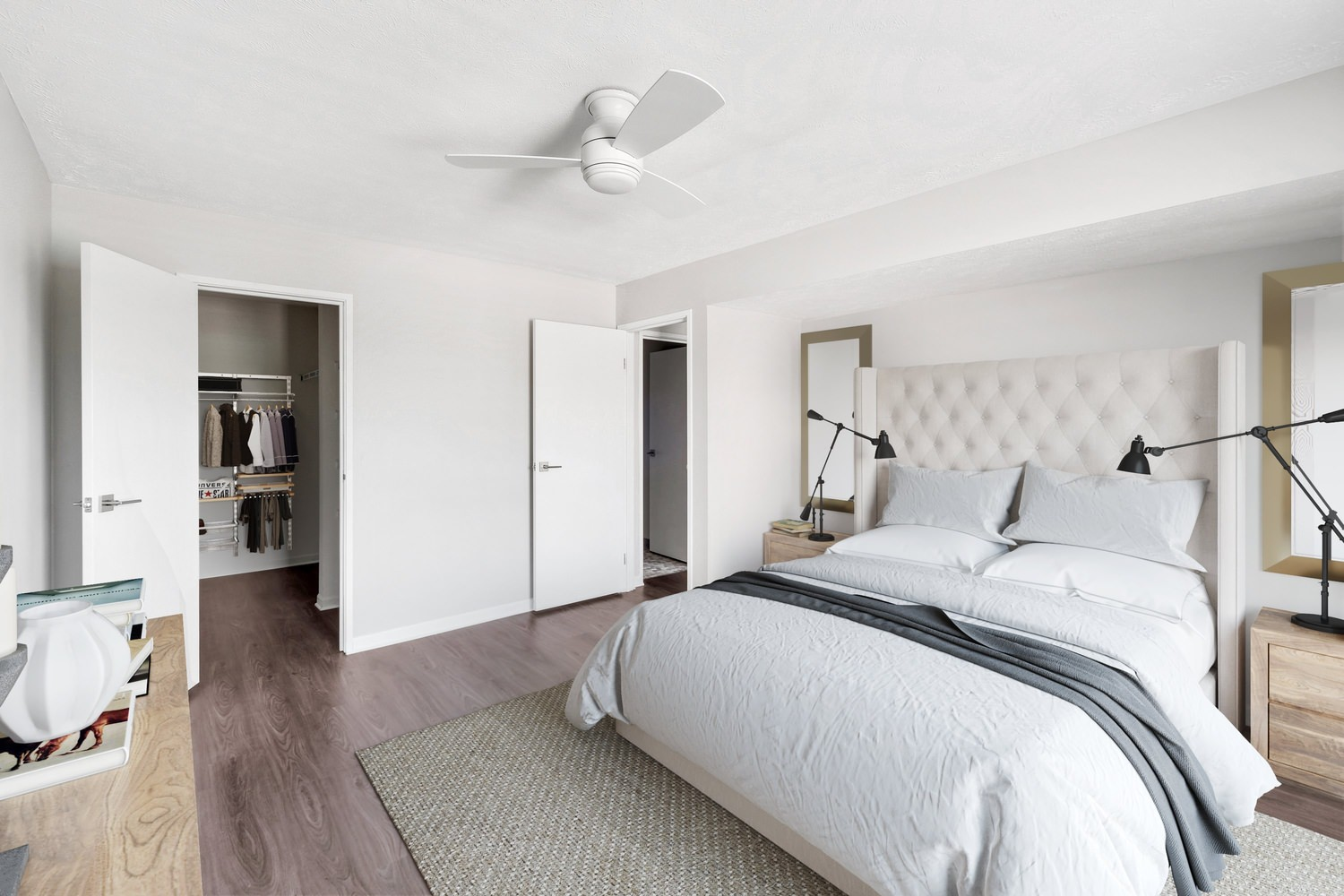 A bedroom that has a bed with white and grey sheets near other wooden furniture.