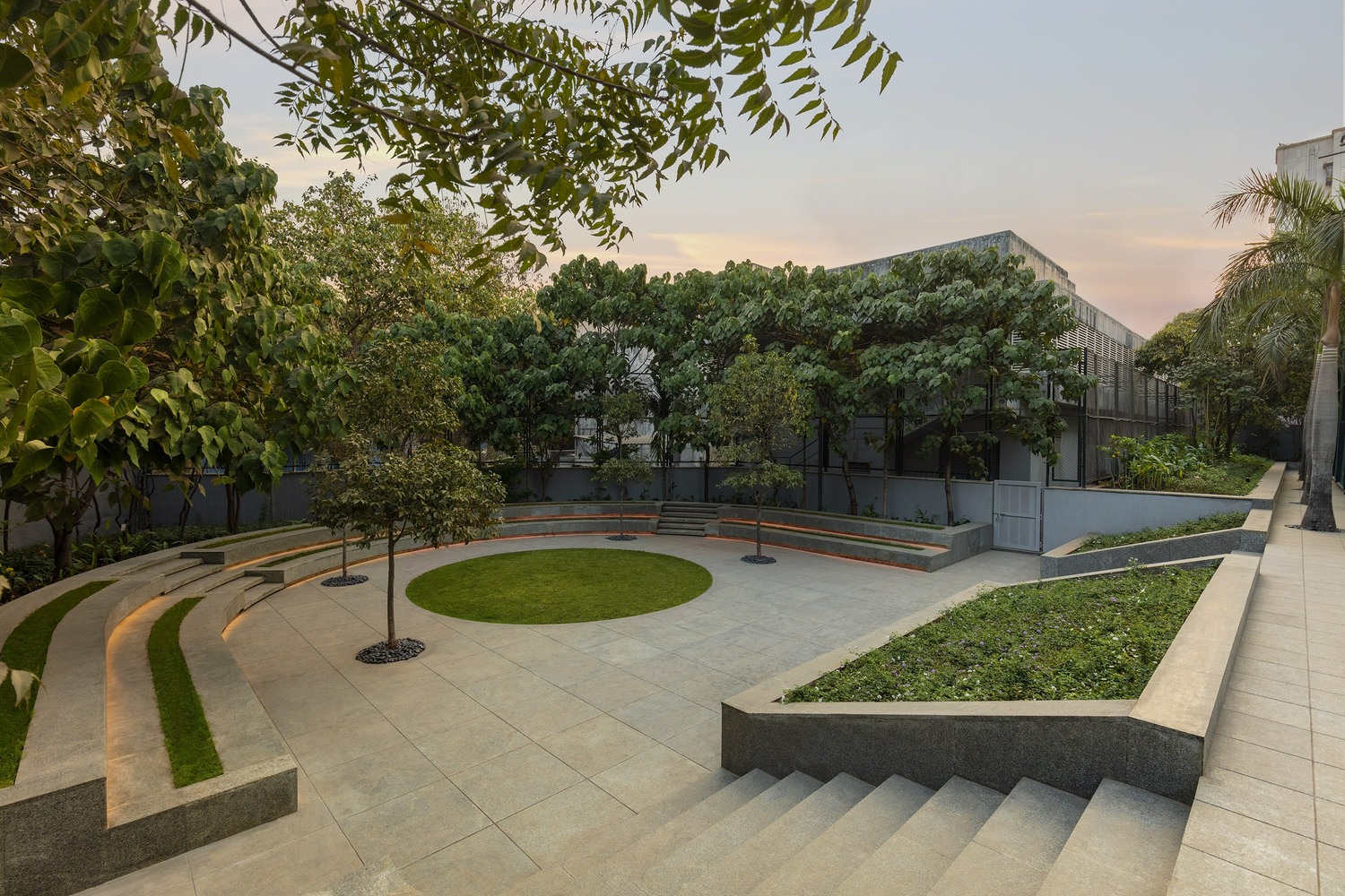 A beautiful view of courtyard in the outdoor with fountains and with lined trees surrounded in the park