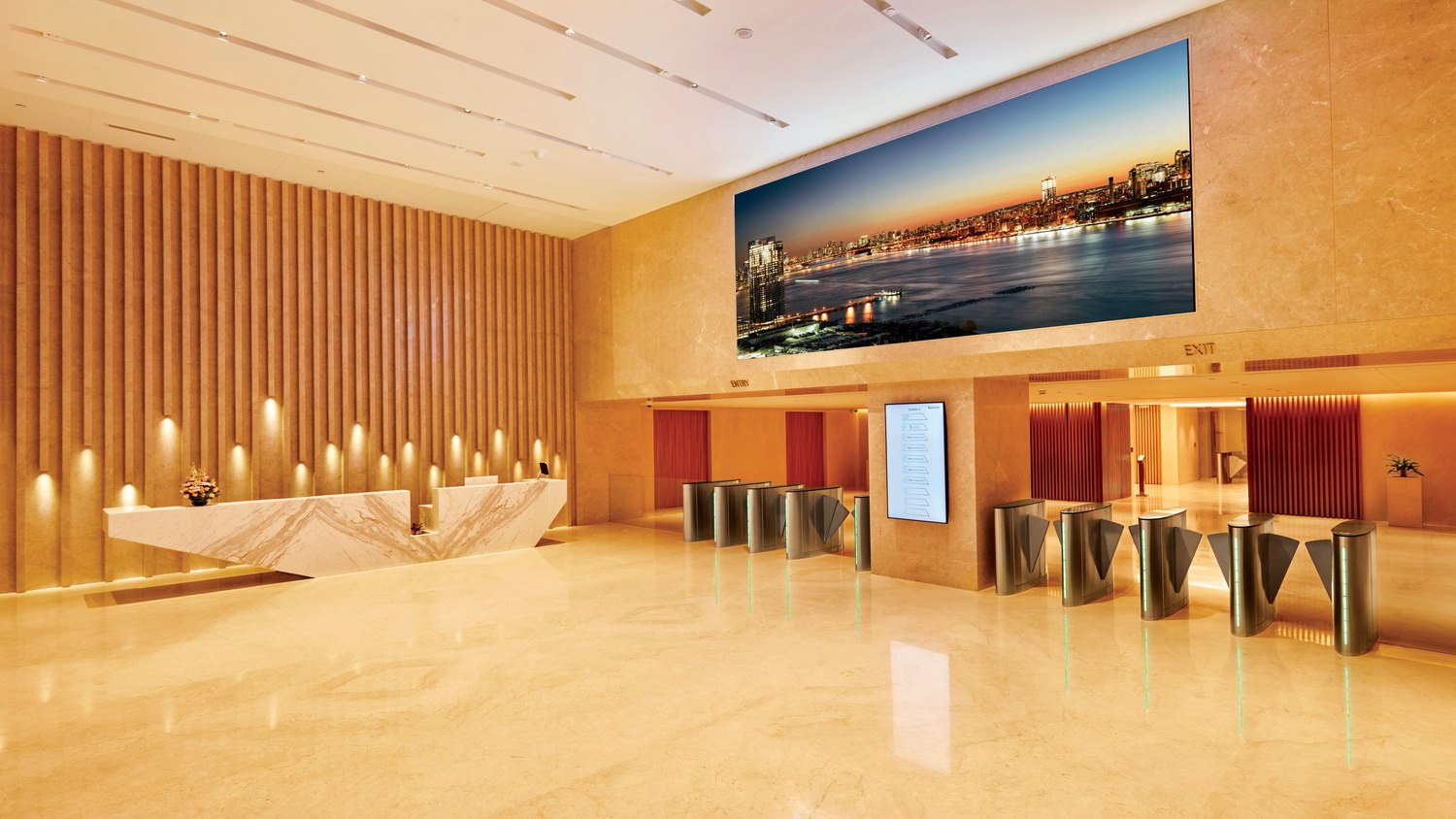 A large lobby with different counters and a large picture of a city skyline at night on the wall.