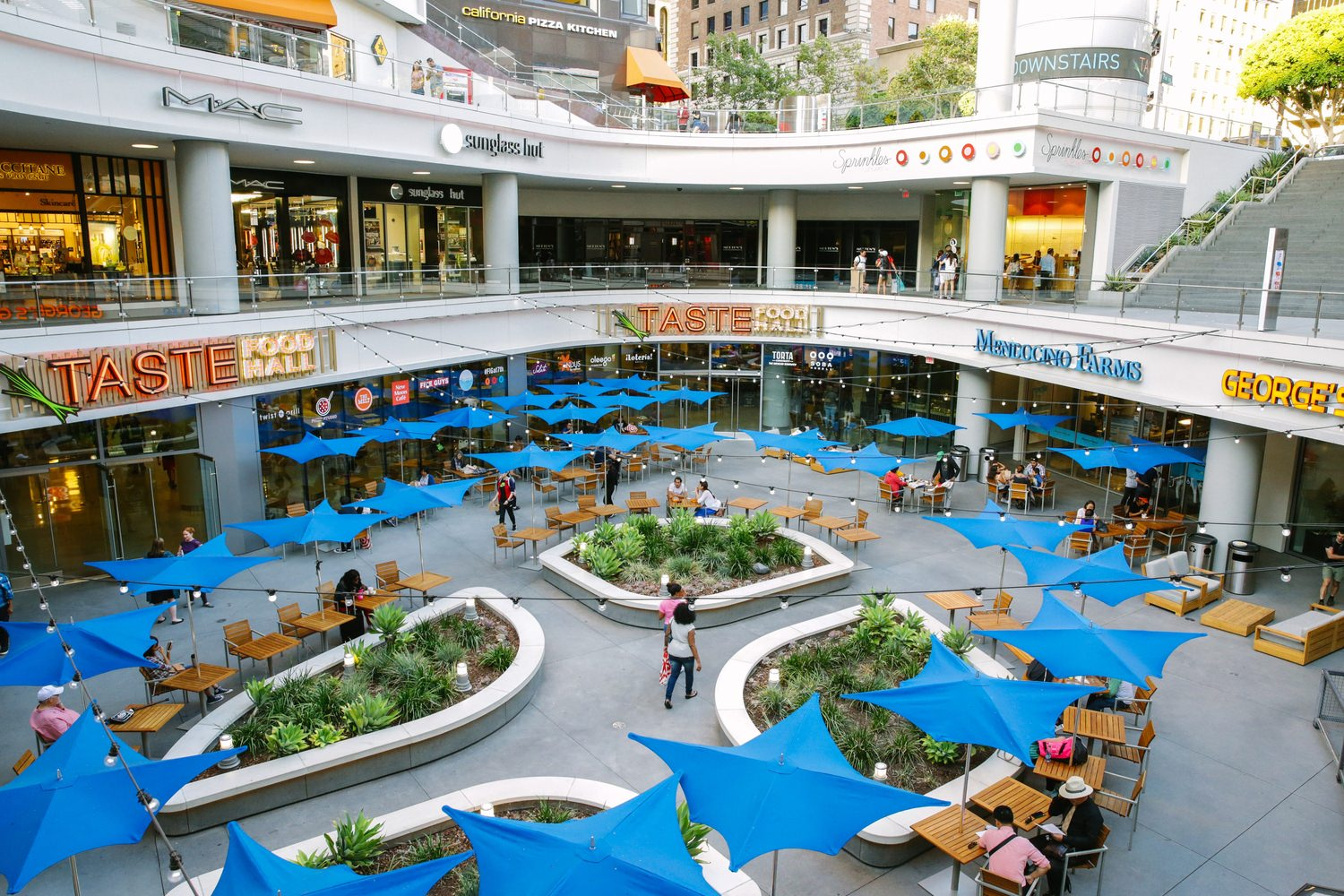 A food court that is in the middle of a mall that has umbrellas above each of the tables.