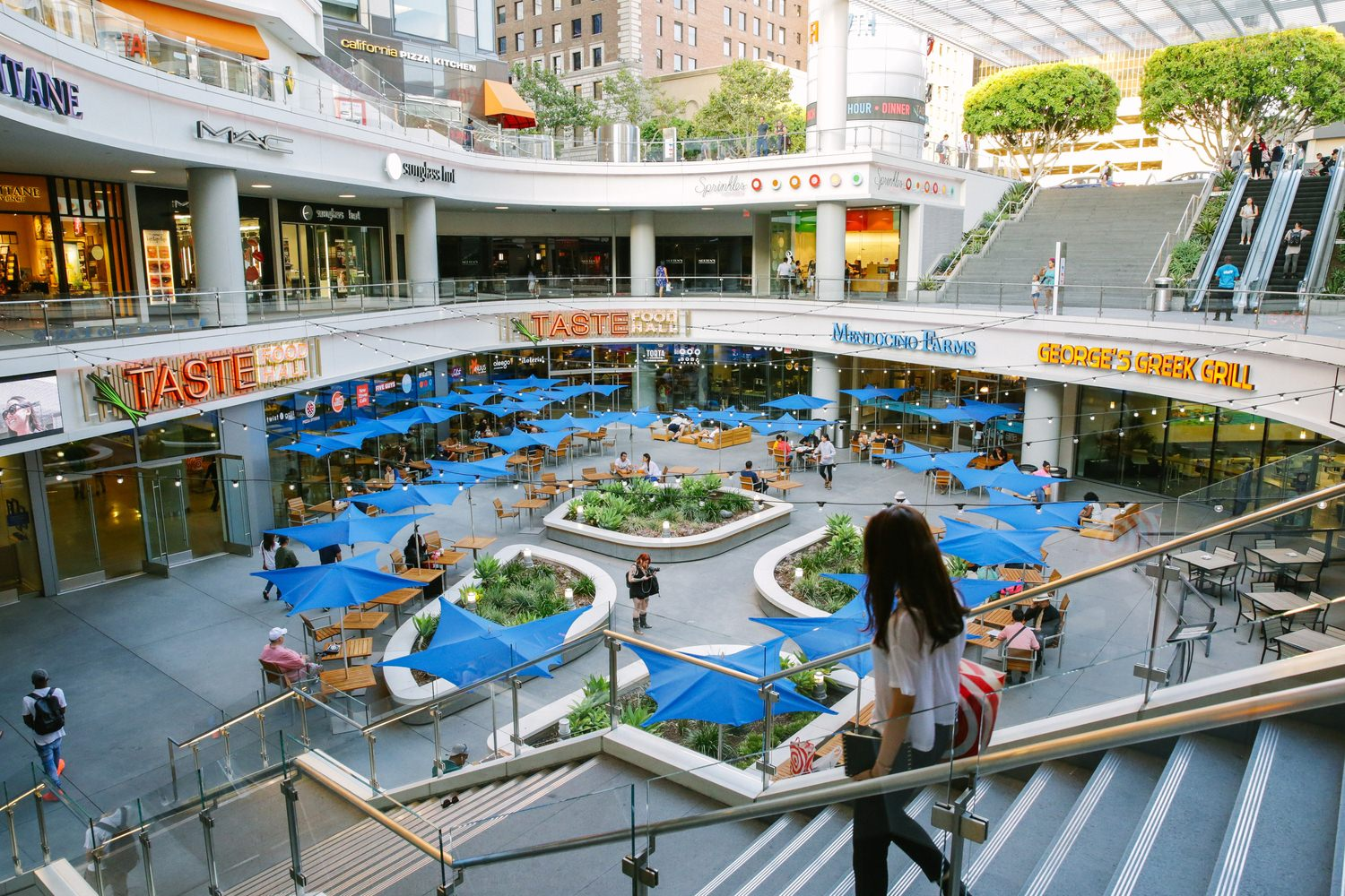 A woman walking down a flight of stairs that leads to a plaza at the shopping mall.