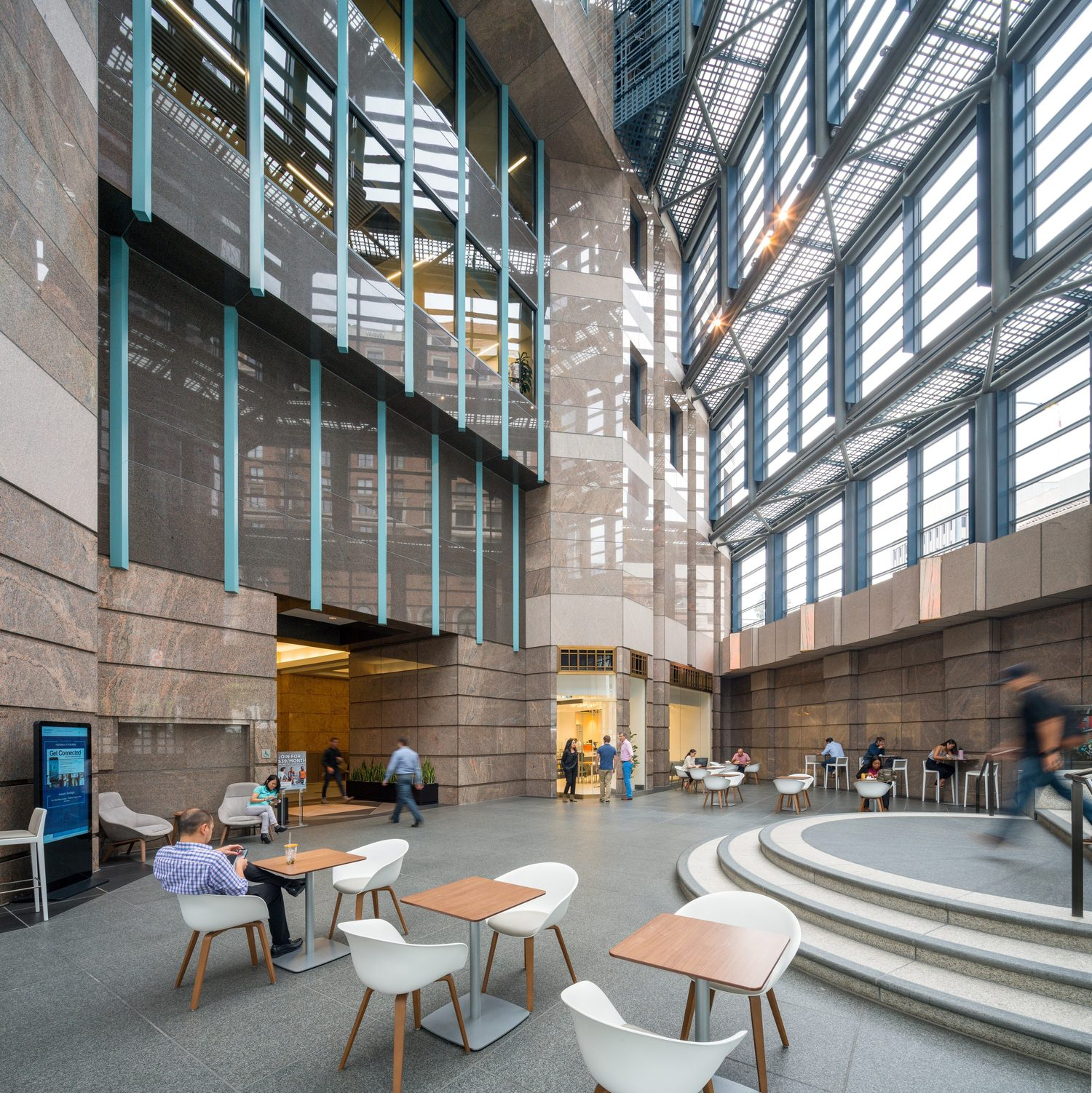 A large lobby that has people sitting and walking along the area within the big building.