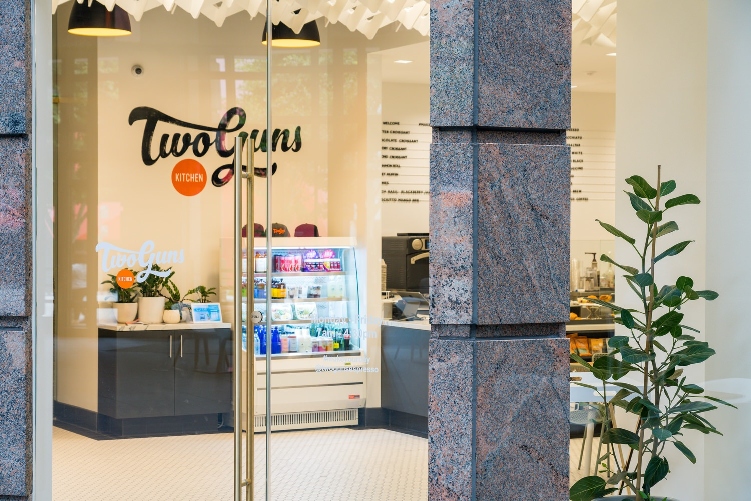 Two guns kitchen lobby showcasing food items at one end and having some potted plants at the other end.