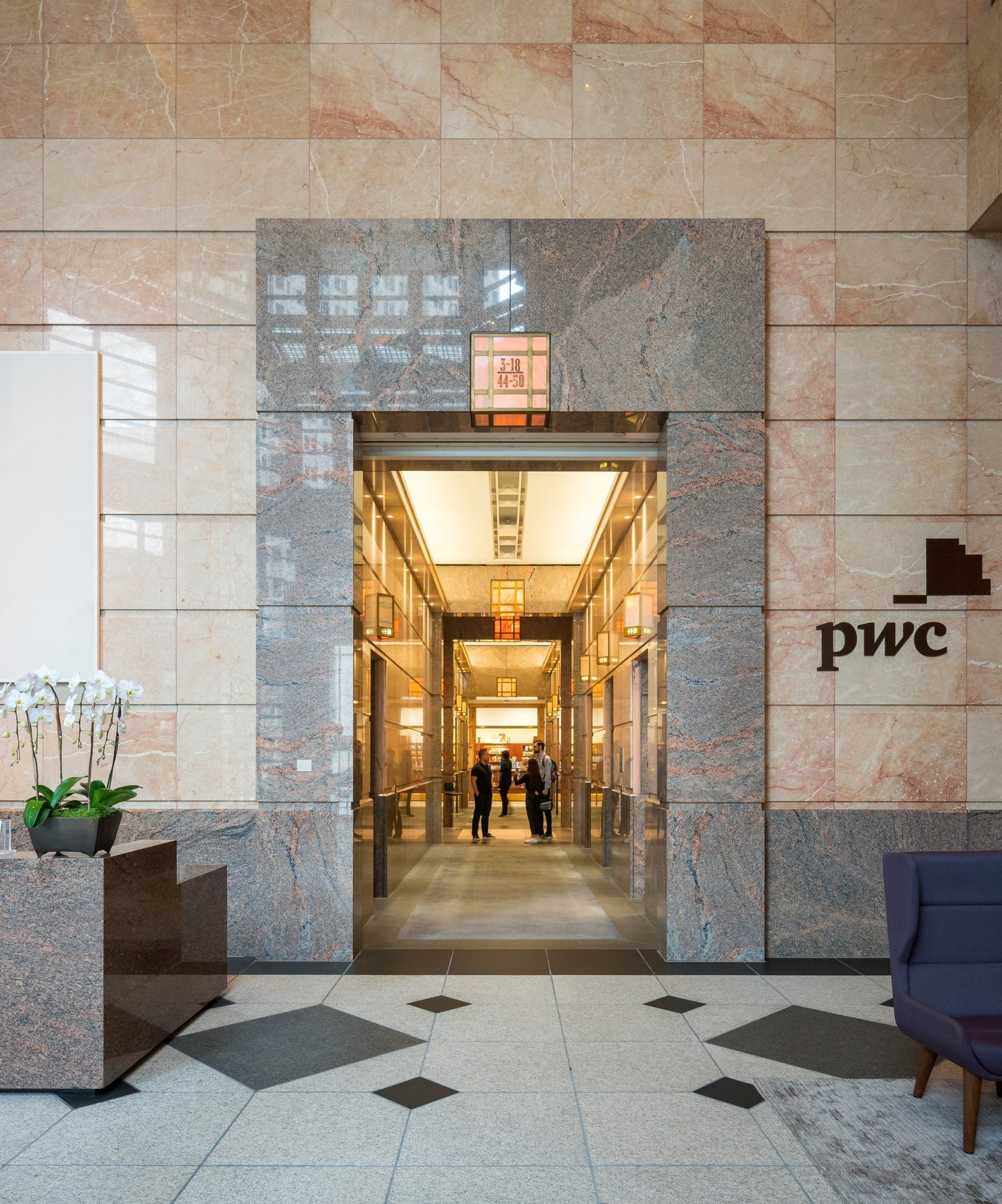 Lobby of the PWC building that has people walking along the long corridor by the elevators.