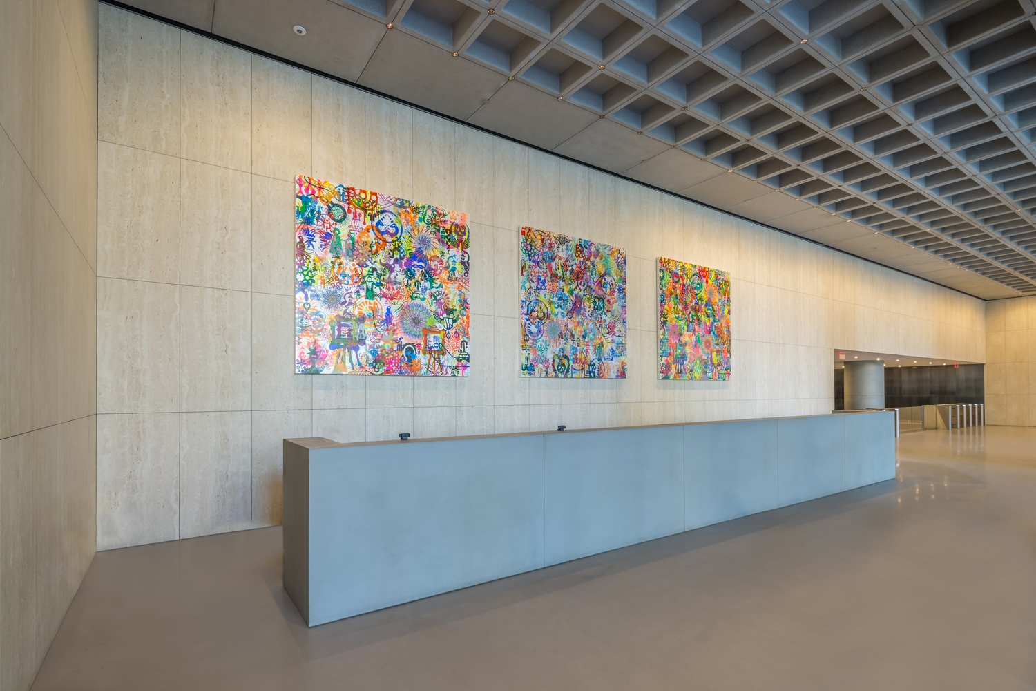 Large lobby that has a long counter in the middle of it and a tiled wall full of paintings.