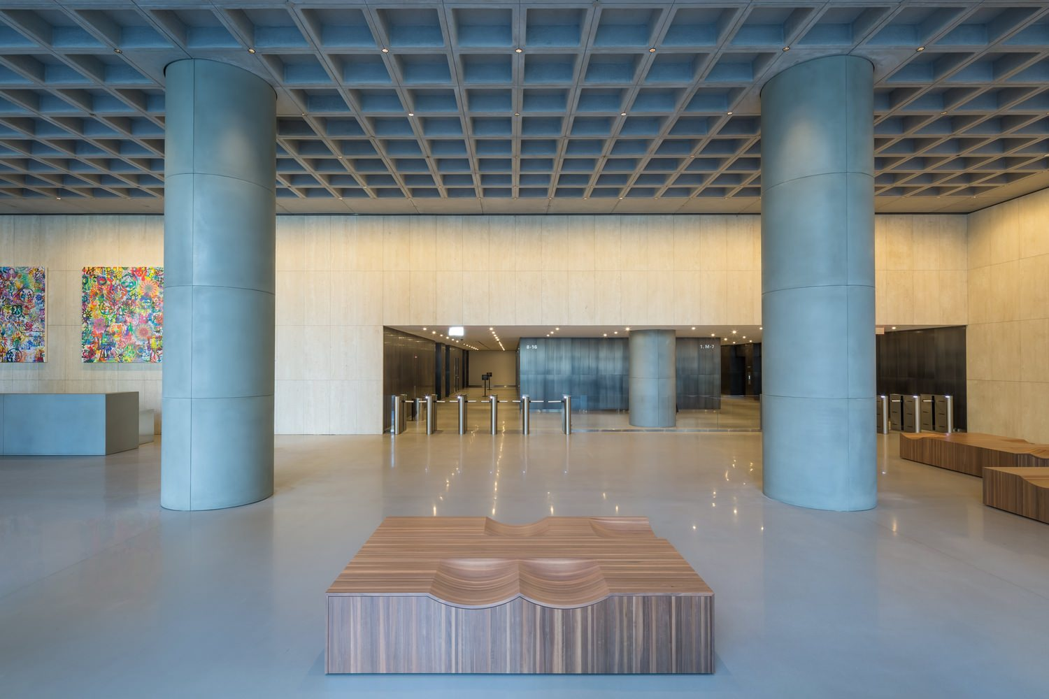 A lobby in a building that has some large concrete pillars as well as some seating areas around the outside of it.