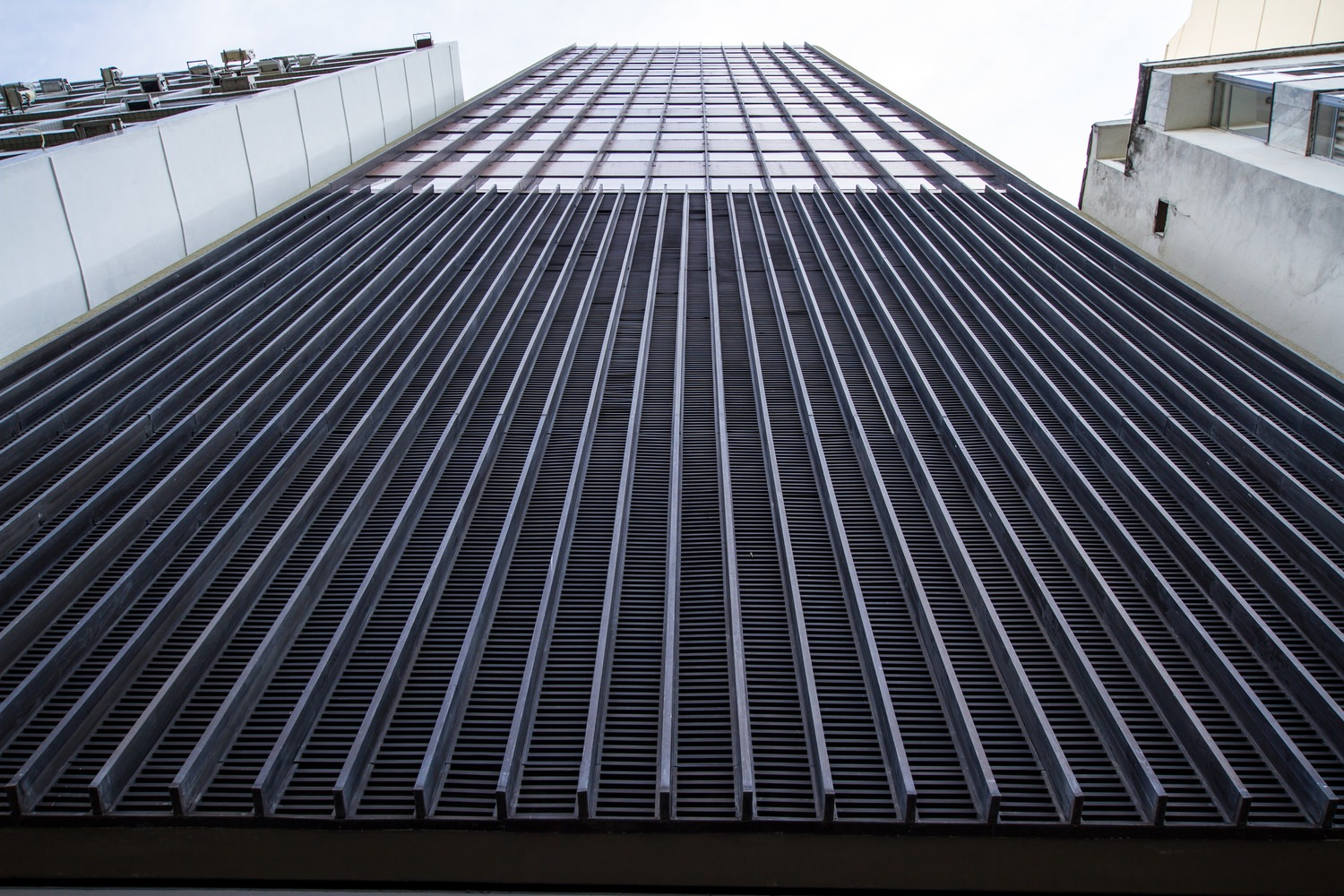Low angle view of the outside of a large building with metal grates on the outside.