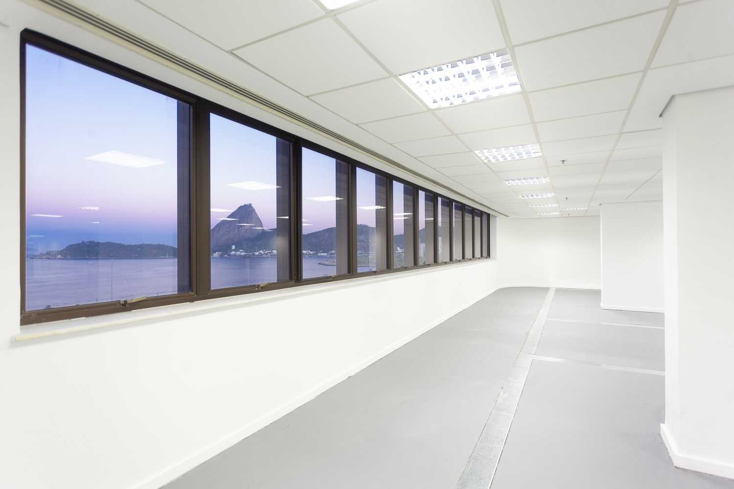A large room that has white columns with a row of windows that shows a view of the harbor.