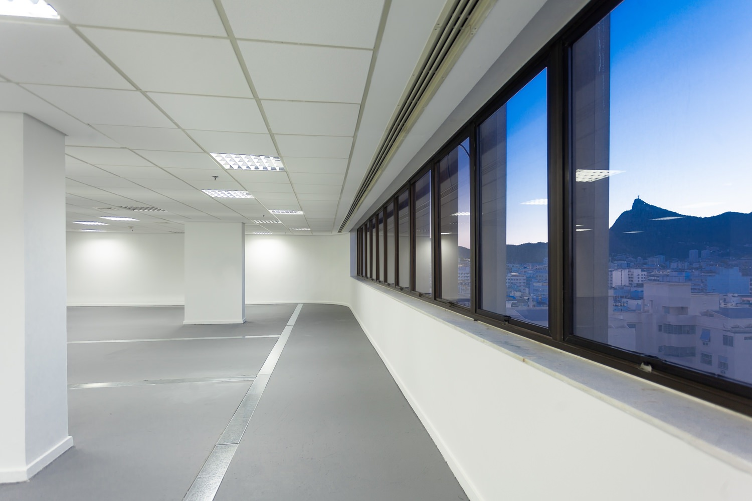A large white room that has a window that shows a view of the city and mountains.