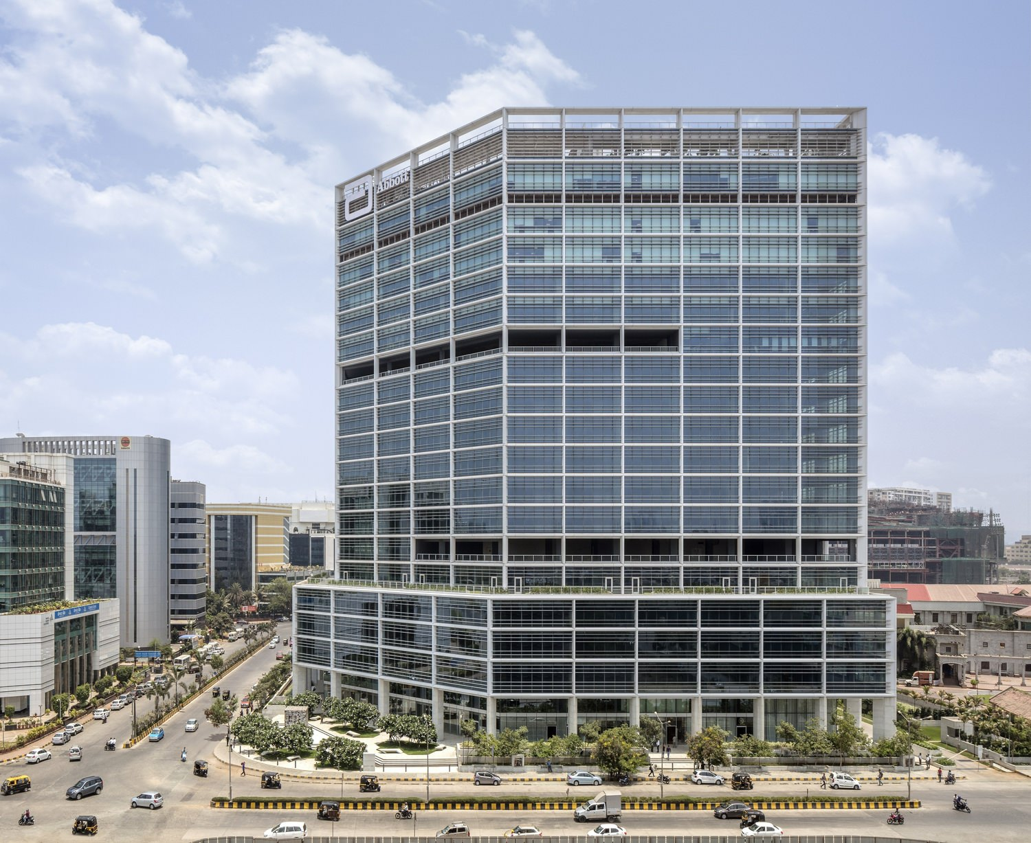A tall office building that is located on a corner in a downtown area and has trees at the base of it.