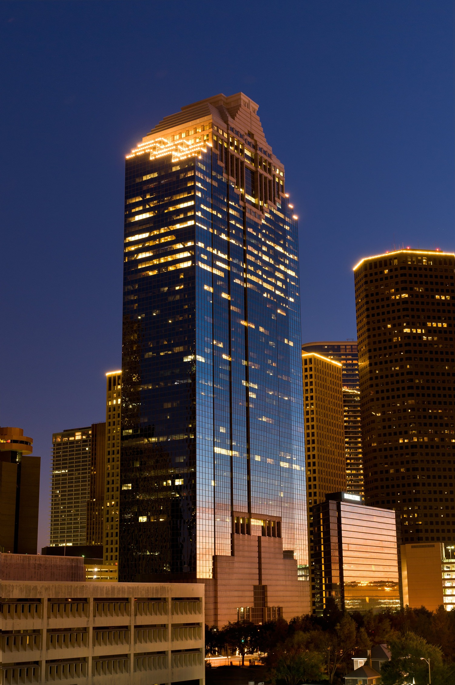 A very tall glass building that is located downtown in a city and the lights are turned on in it at night.Plaza