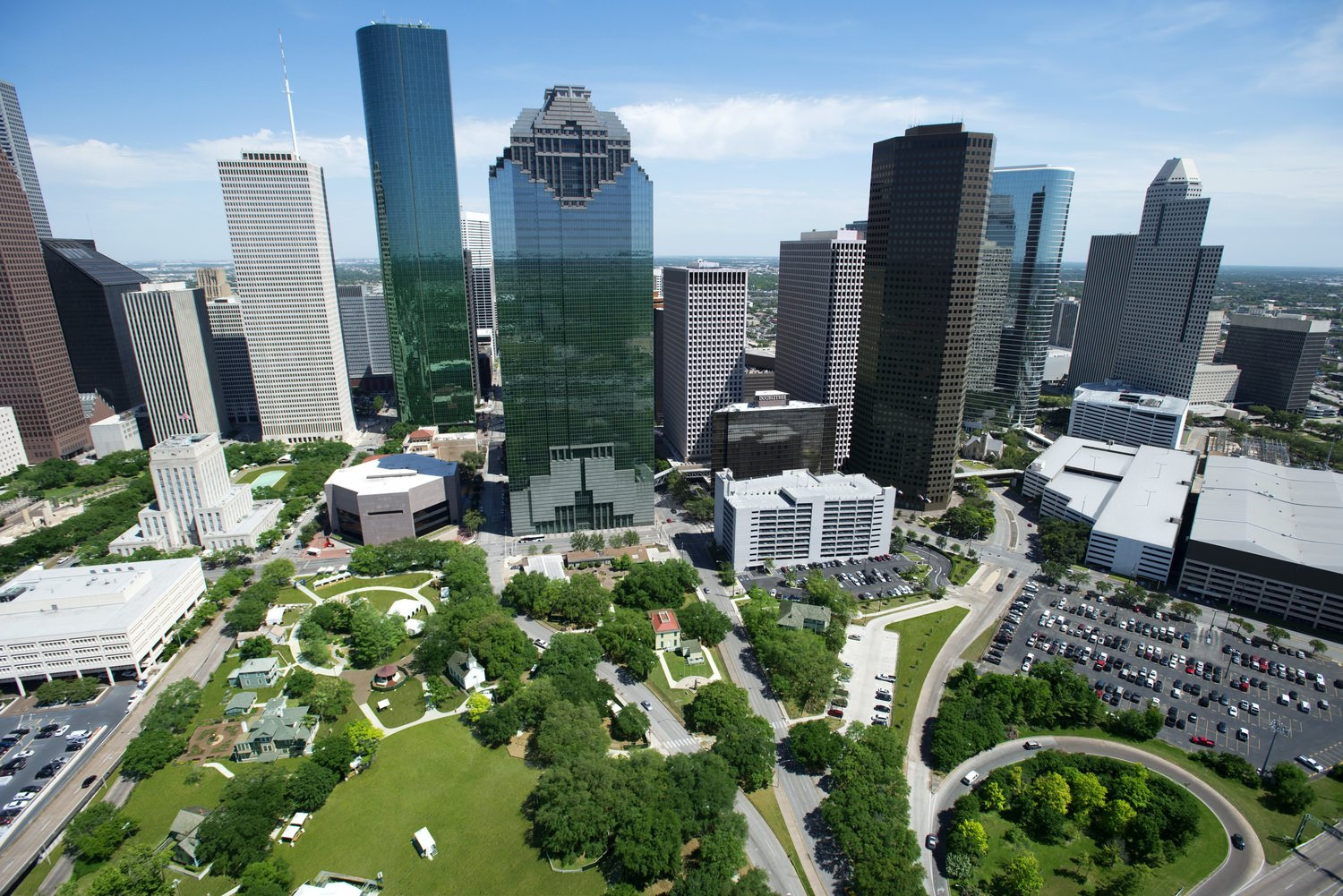 A view of a park that has trees and grass that is located in the middle of a city that has tall buildings in it.