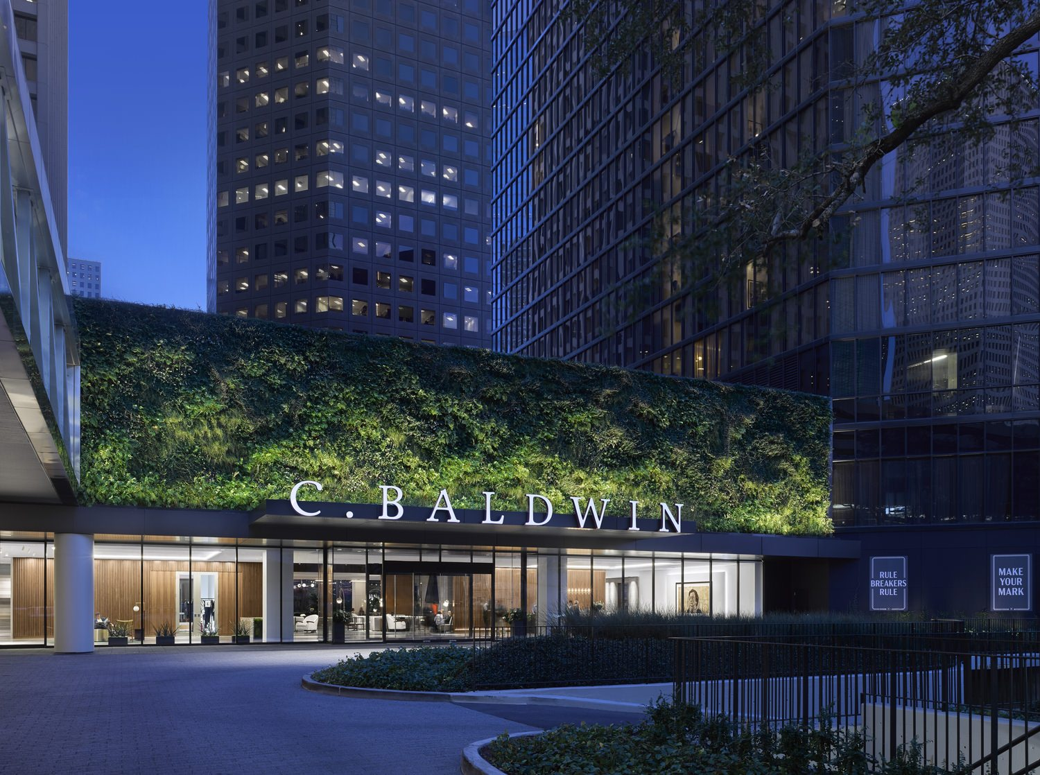 A building with a C. Baldwin logo in the front of it and there is a lot of plants that are around the sign area.