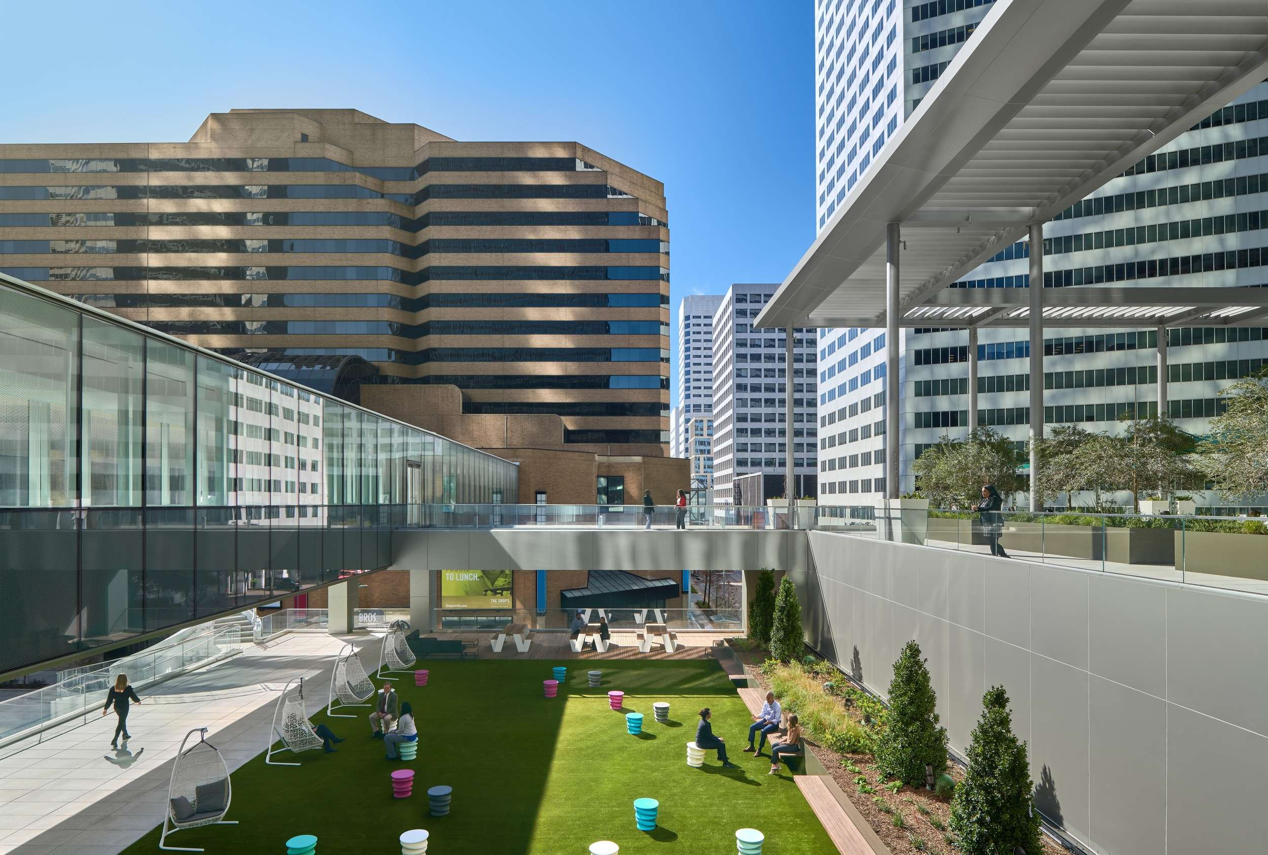 A park that is located between some buildings in a downtown area with some seating area.