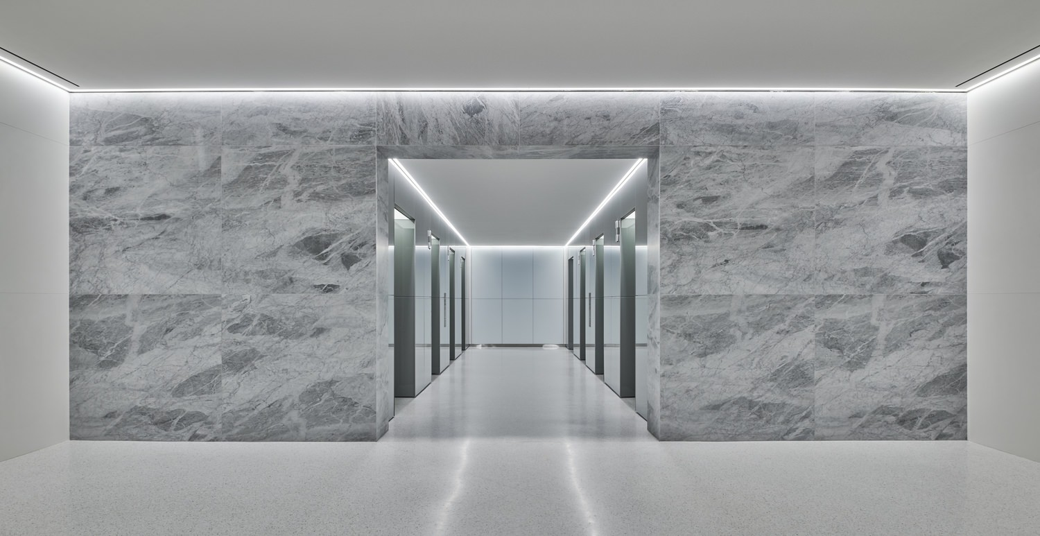 A view down a hallway in a building that has stone walls and there are elevators on either side of the hallway.