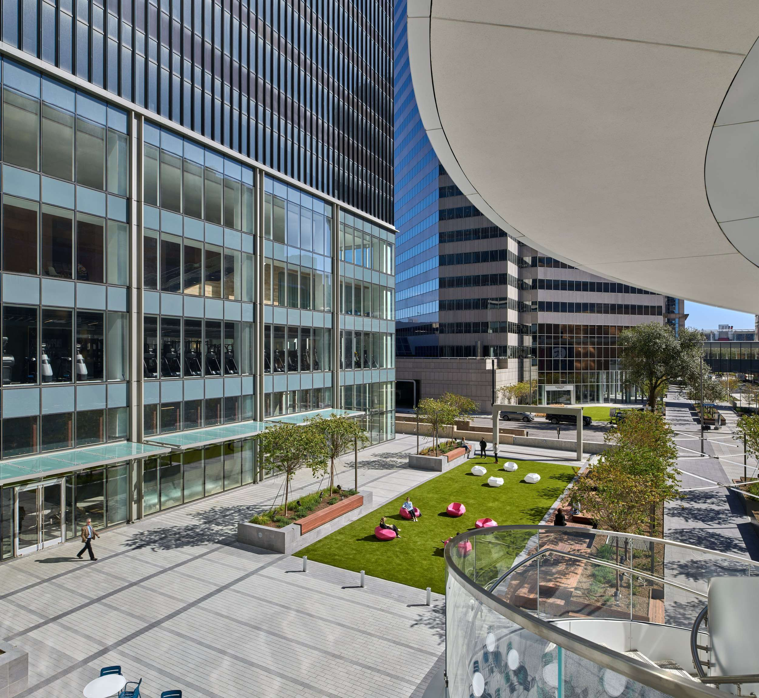 A view of a park that is in front of a large glass building and it has chairs sitting on the grass o