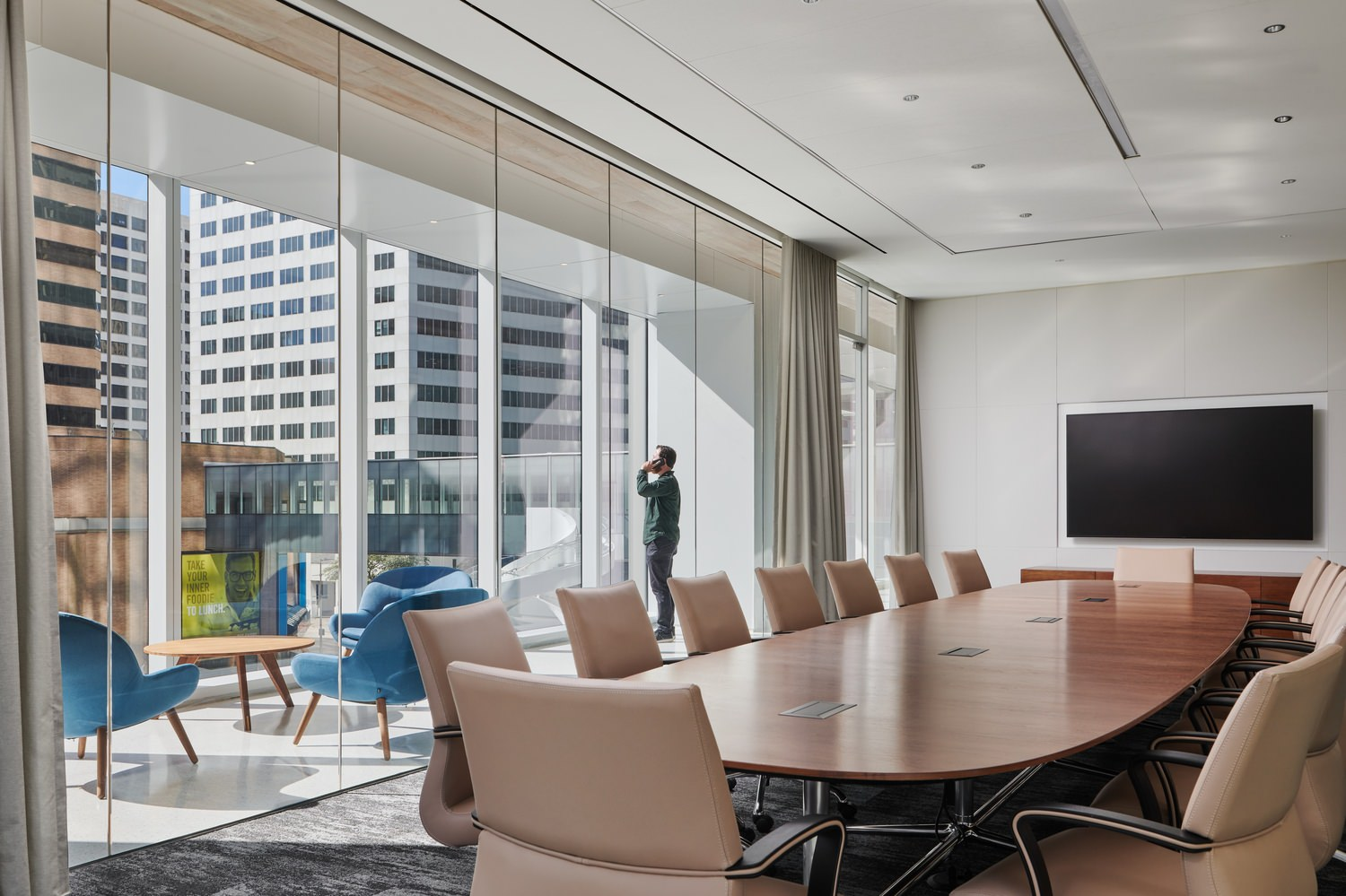 A board room that has a large table in the middle of it and a lot of chairs around it as well as a TV on a wall.