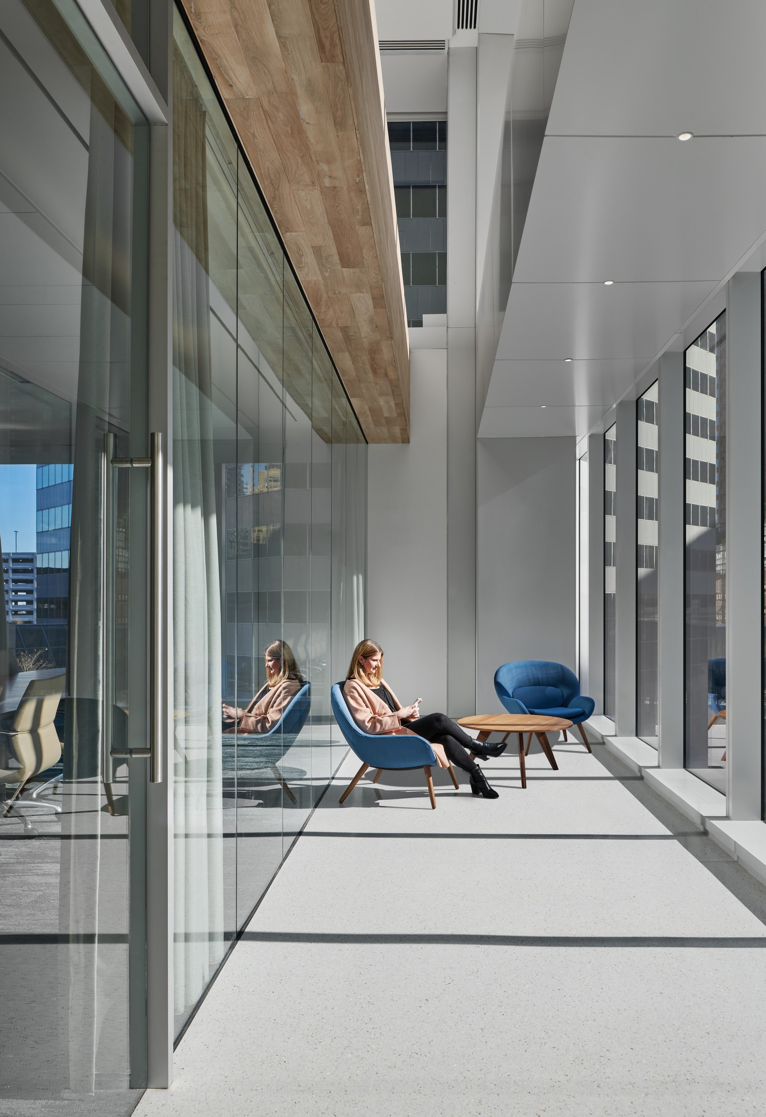 A person that is sitting in a lounge chair in an office area in front of a glass wall that leads to other rooms.