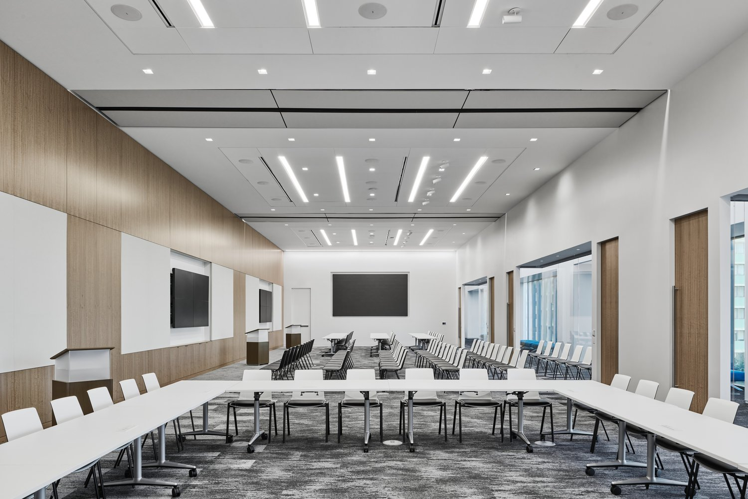 A large conference room in an office that has large desks with a lot of chairs around it.