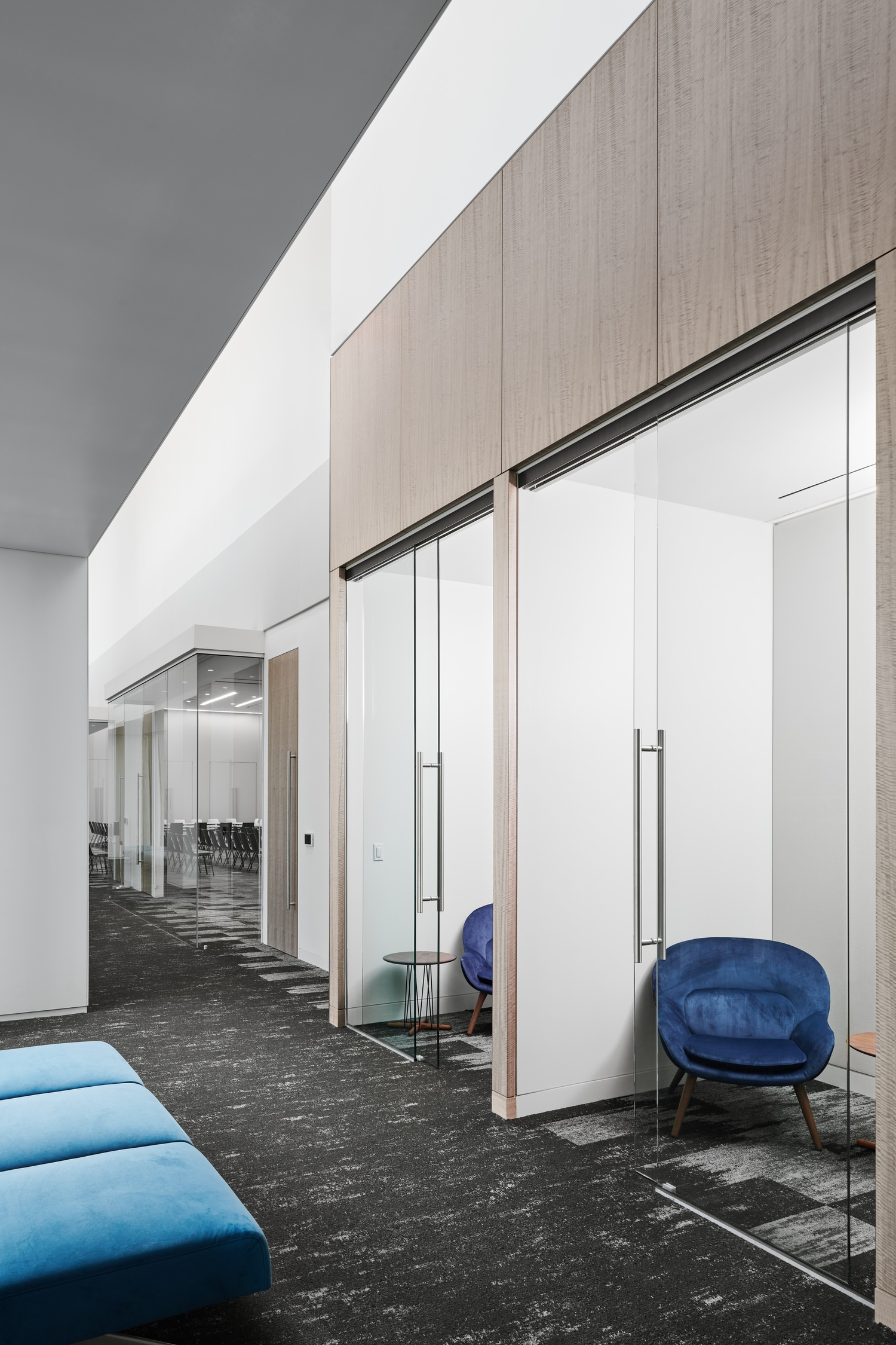 A room that has a blue chair in it and then there are small working areas with glass doors.