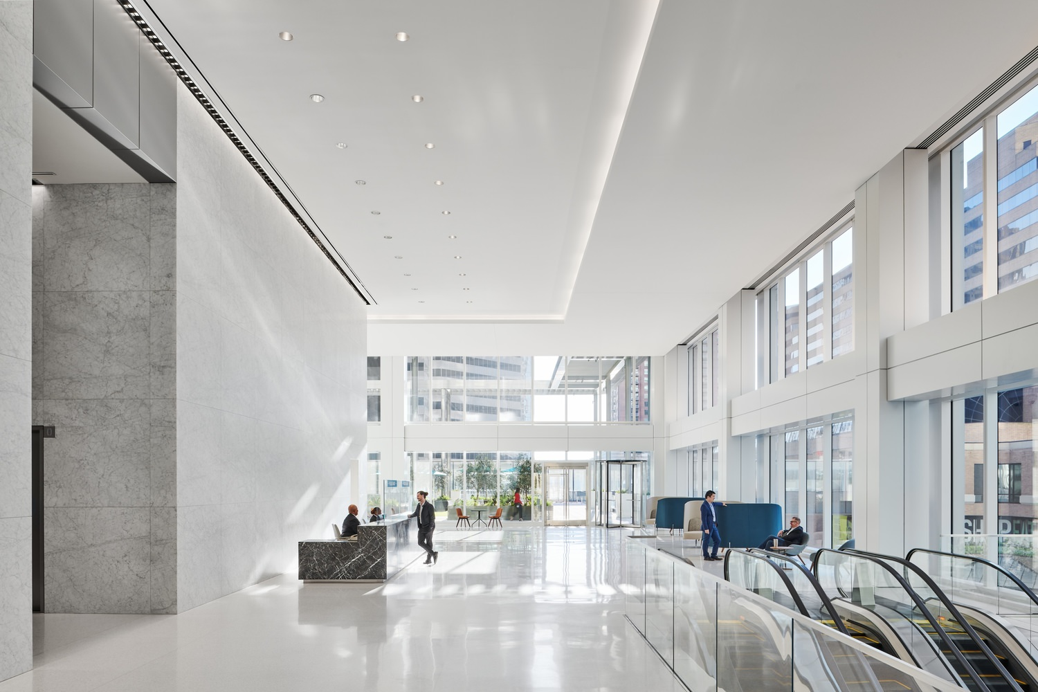 A man speaks to a receptionist in a bright lobby.