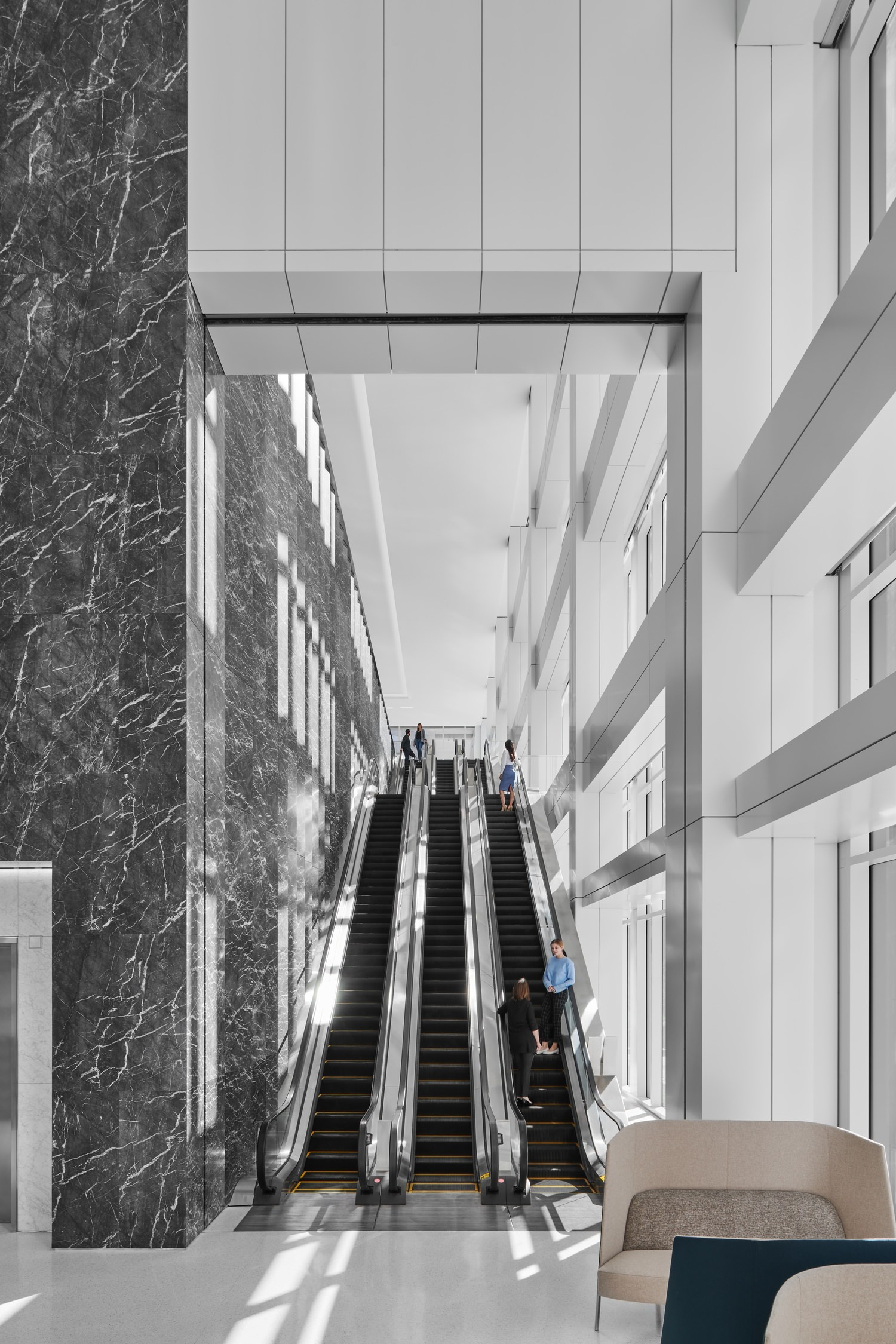 An escalator goes up to another level inside a white and black marbled building.