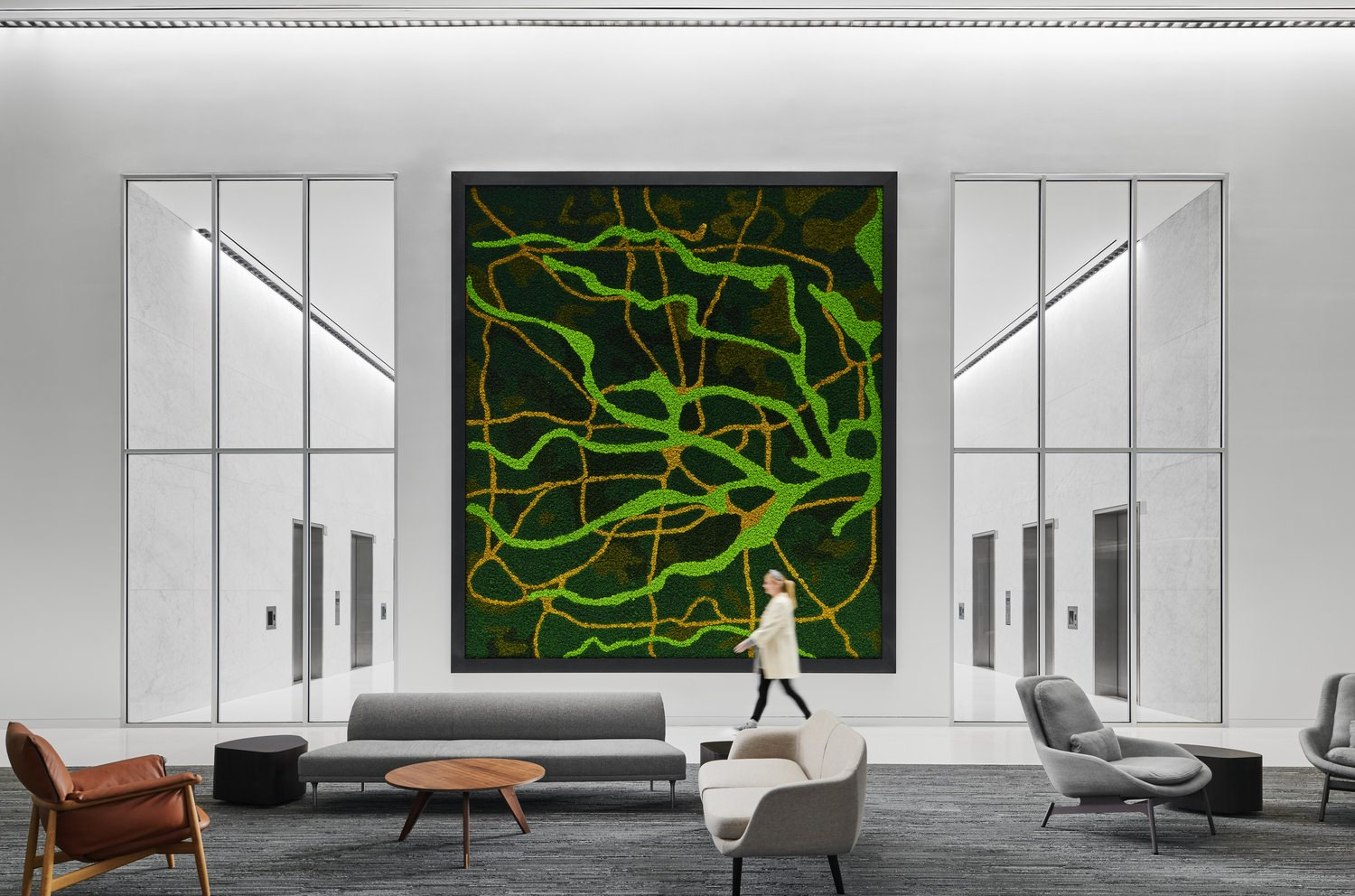 A woman walks across a building lobby. A large green mural hangs on the wall directly in front of the frame.