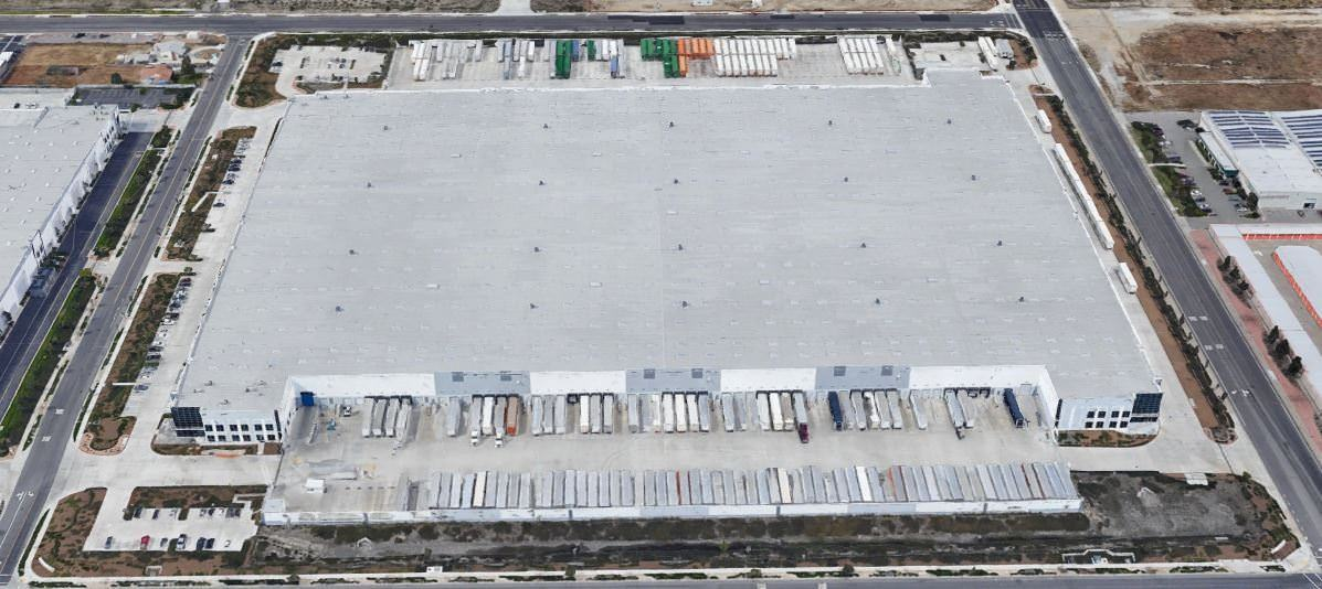 Top view of a large white warehouse building that has trucks parked in the delivery area.