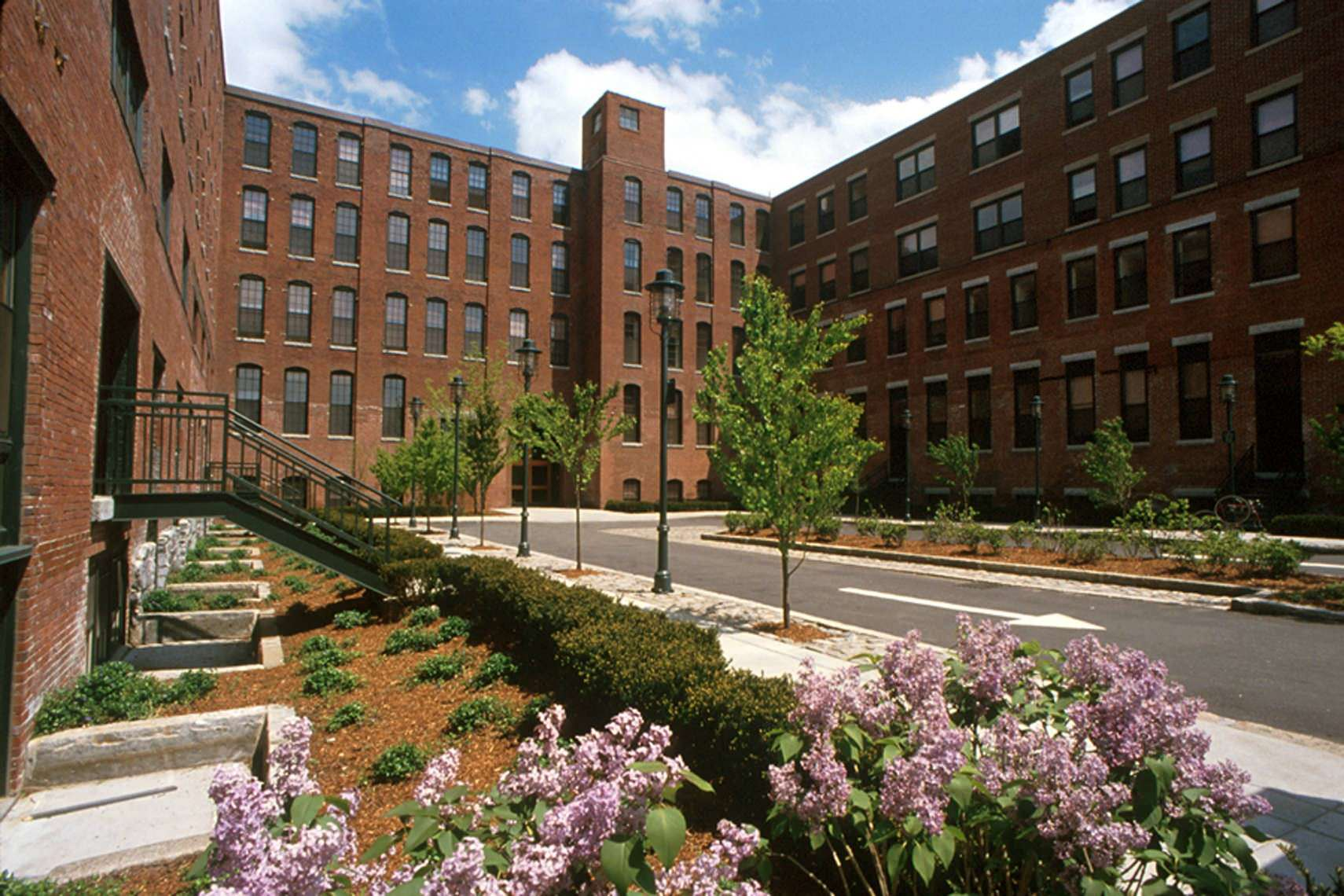 The courtyard of a large brick building that has trees and plants in it as well as a sidewalk around
