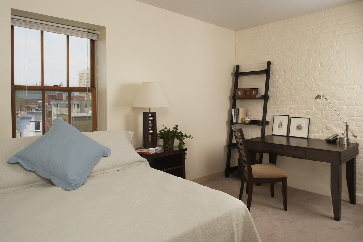A bedroom that has a bed with white sheets on it and a desk that is up against the wall.