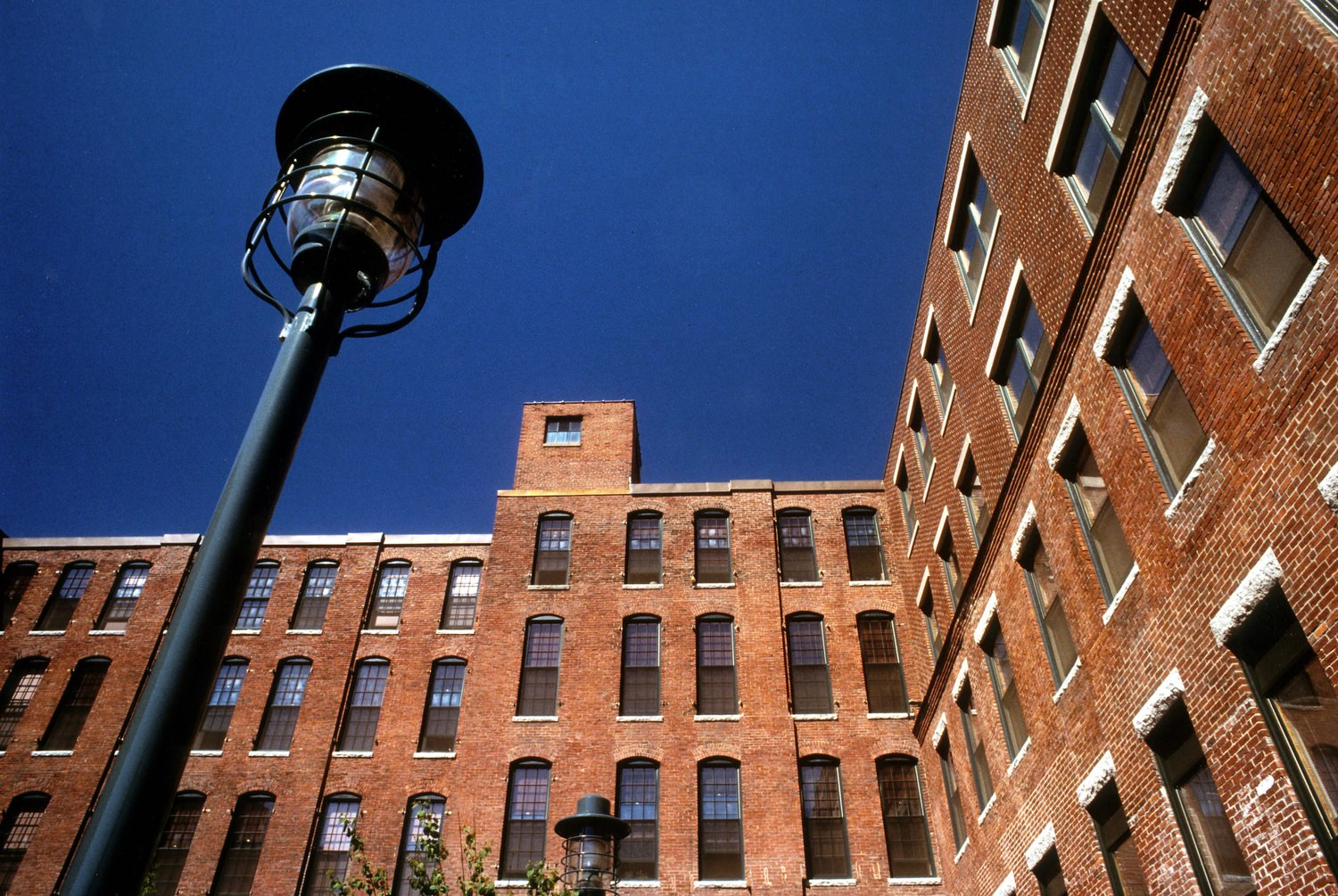 A large brick building that has some black metal lamp posts out front of it and a lot of windows on the building.
