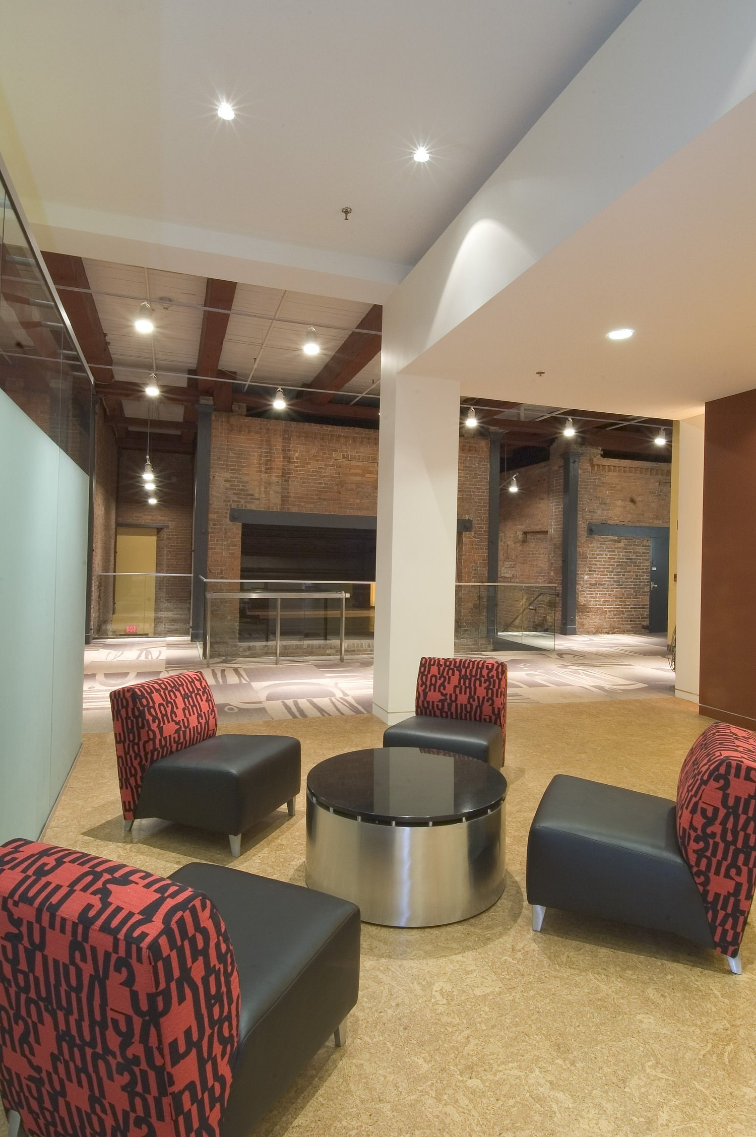 A sitting area that is located in the lobby of a building with four chairs around one table.