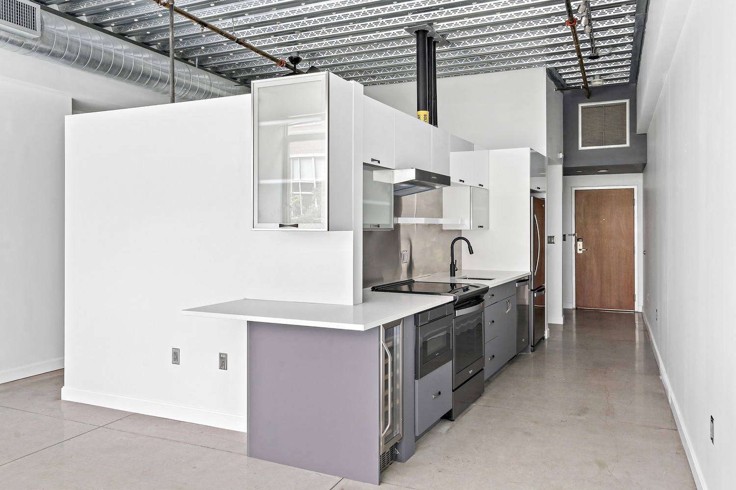 Kitchen and living room area of an apartment that has white walls and tiled floors.