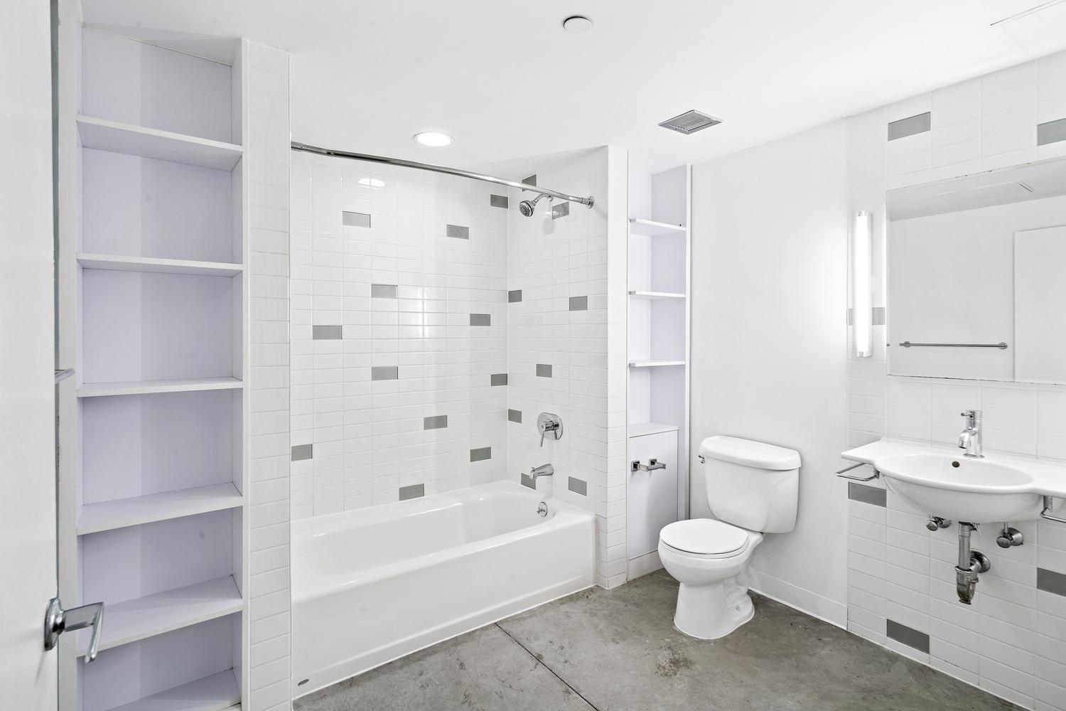 A bathroom with white tiles on the walls and a toilet on top of a marbled floor.