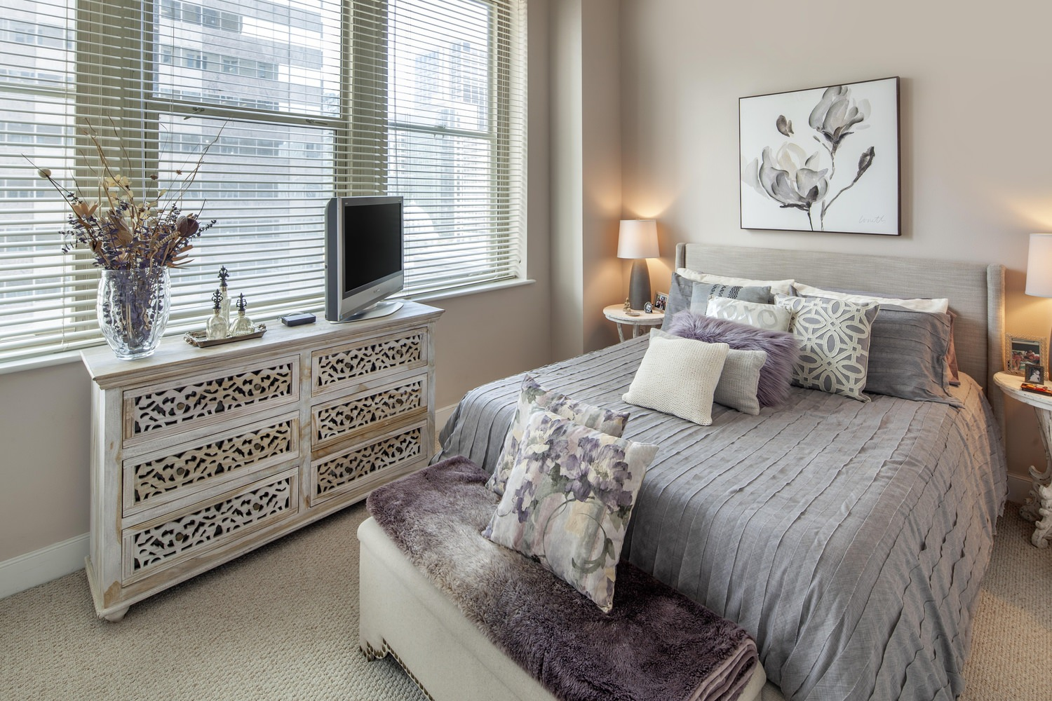 A bedroom that has a bed covered in grey sheets with a window showing the city outside.