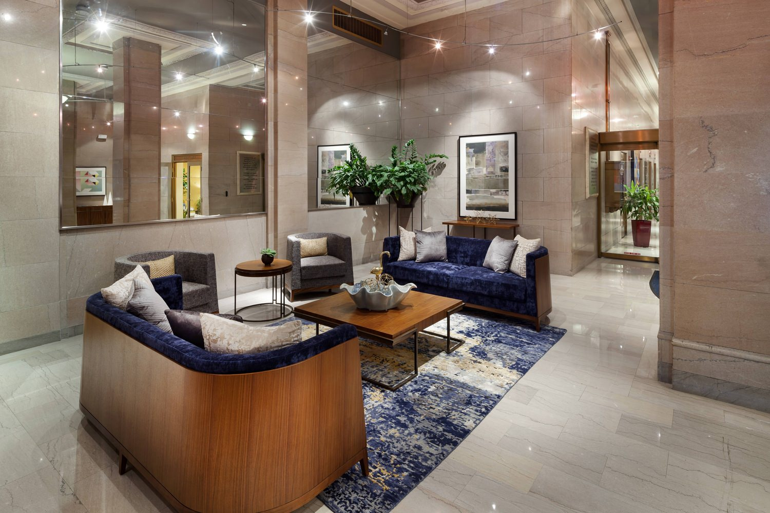 Lobby of a building that has tables and couches in the middle of it with a large mirror on the wall.