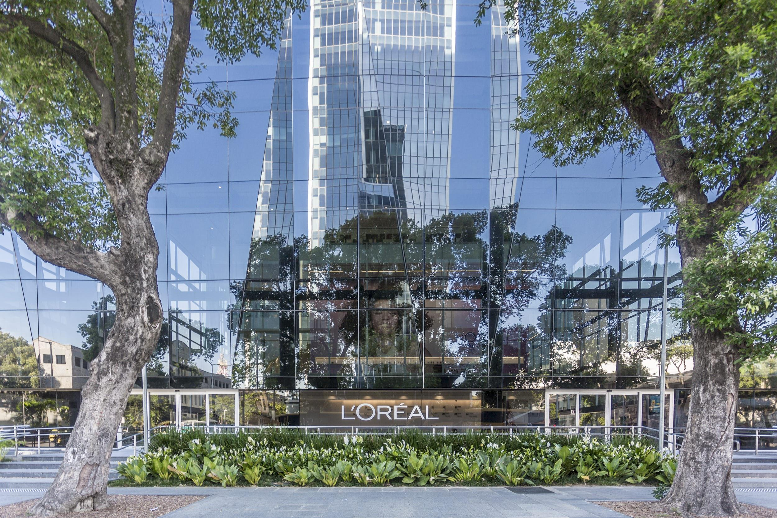 A photo taken from the sidewalk that is in front of a building that has a L'oreal sign on the front