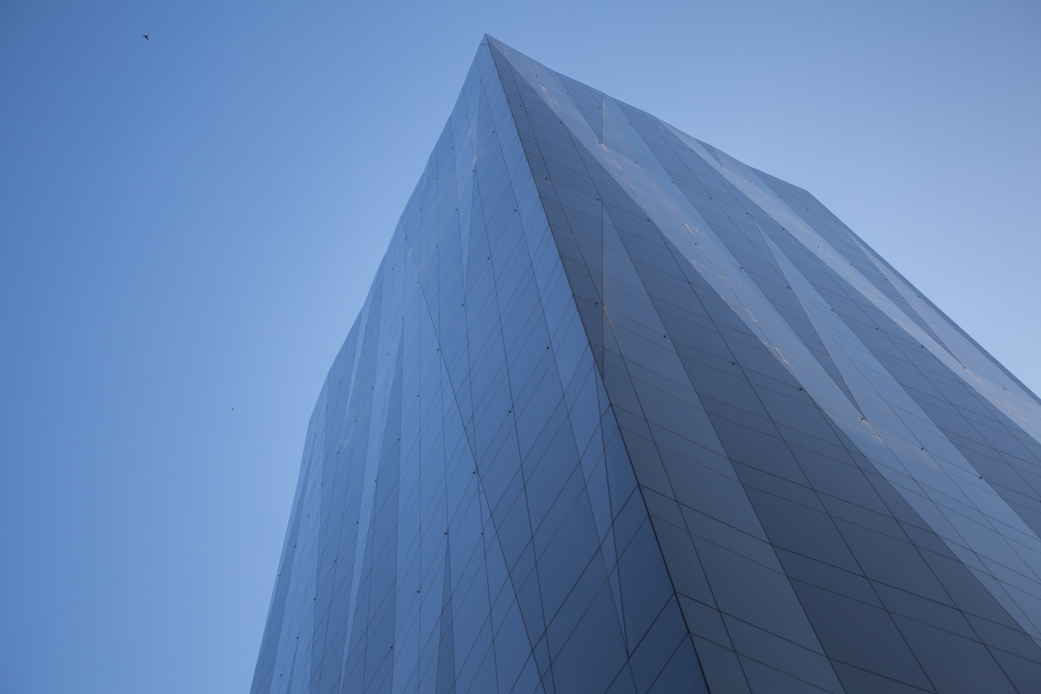 Upward view of a large grey building that is covered in glass windows that is under a blue sky.