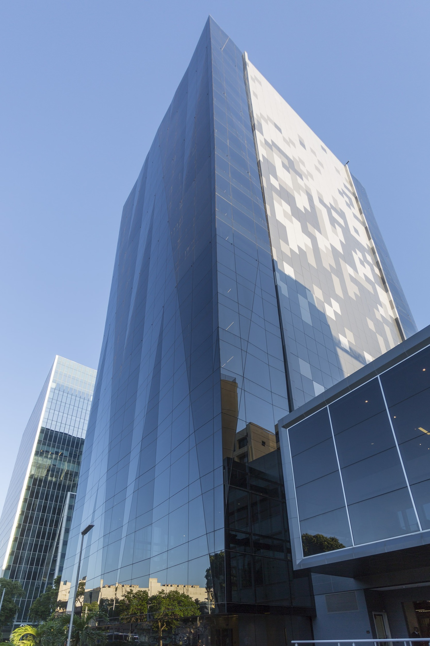 A skyscraper that is covered in glass windows next to other buildings under the blue sky.