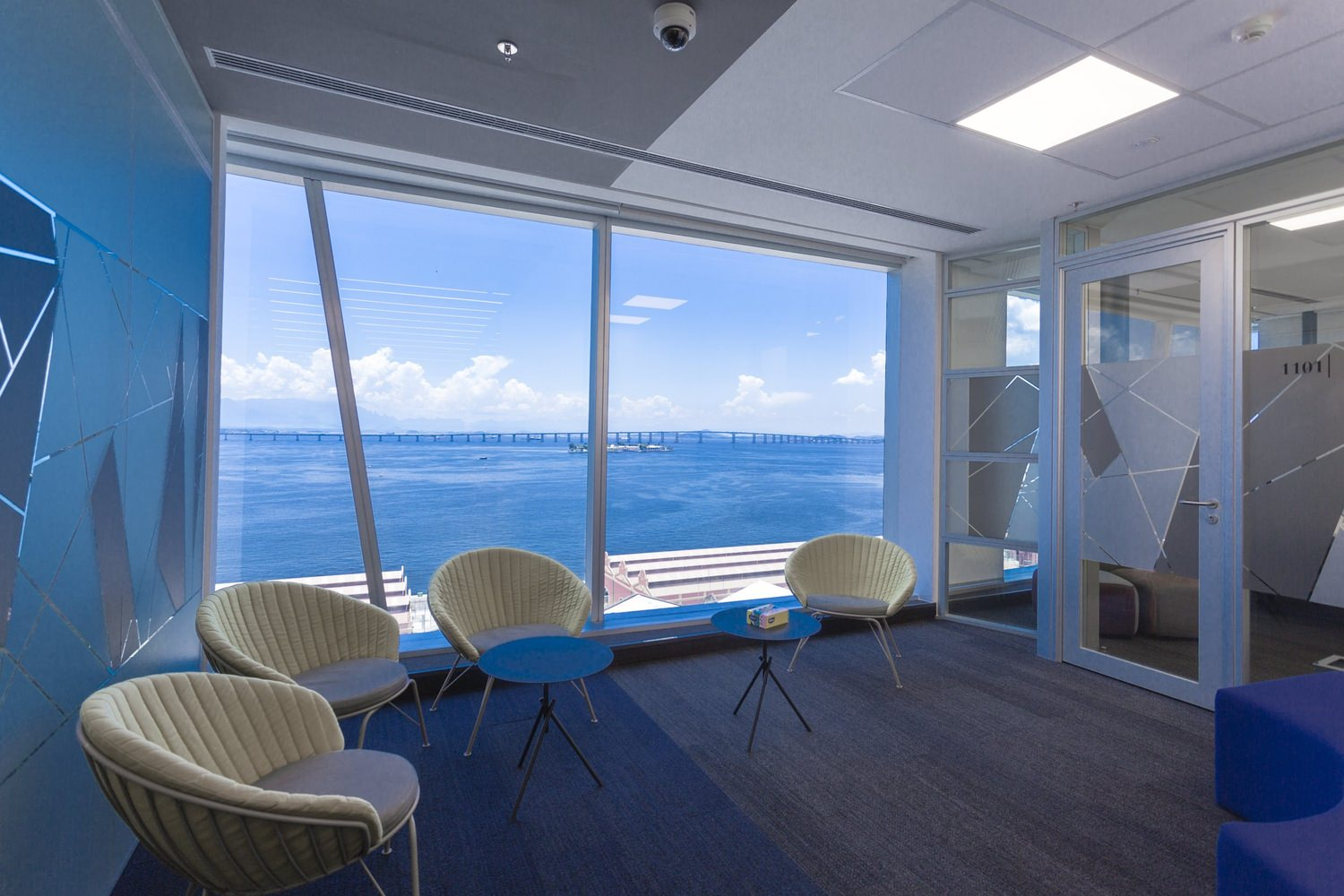 A sitting room that has a large glass window that looks out at the ocean from there and there are four chairs in it.