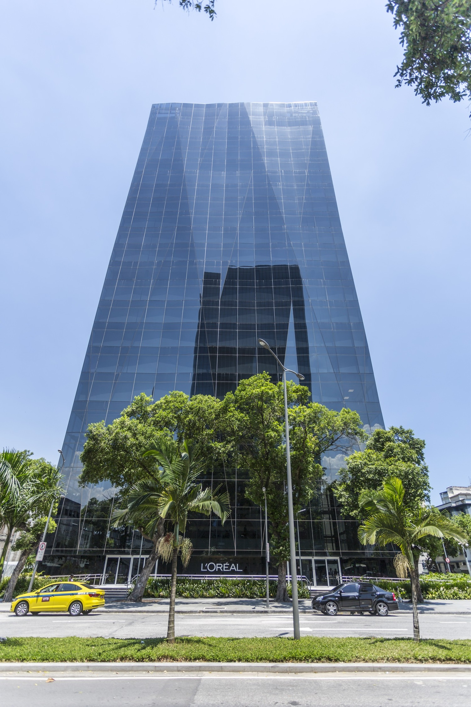 The outdoor view of a tall building with tree in front of the building in the road and has a view of sky with tower