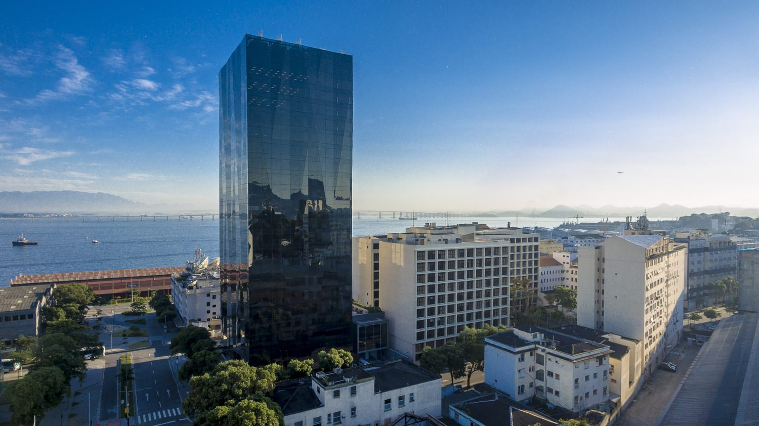 A tall building with black tinted windows the middle of a city that is near a body of water.