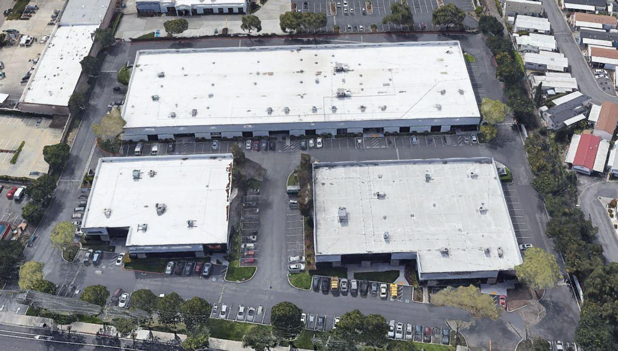 An aerial view of some warehouses that have large parking lots around them with many cars.
