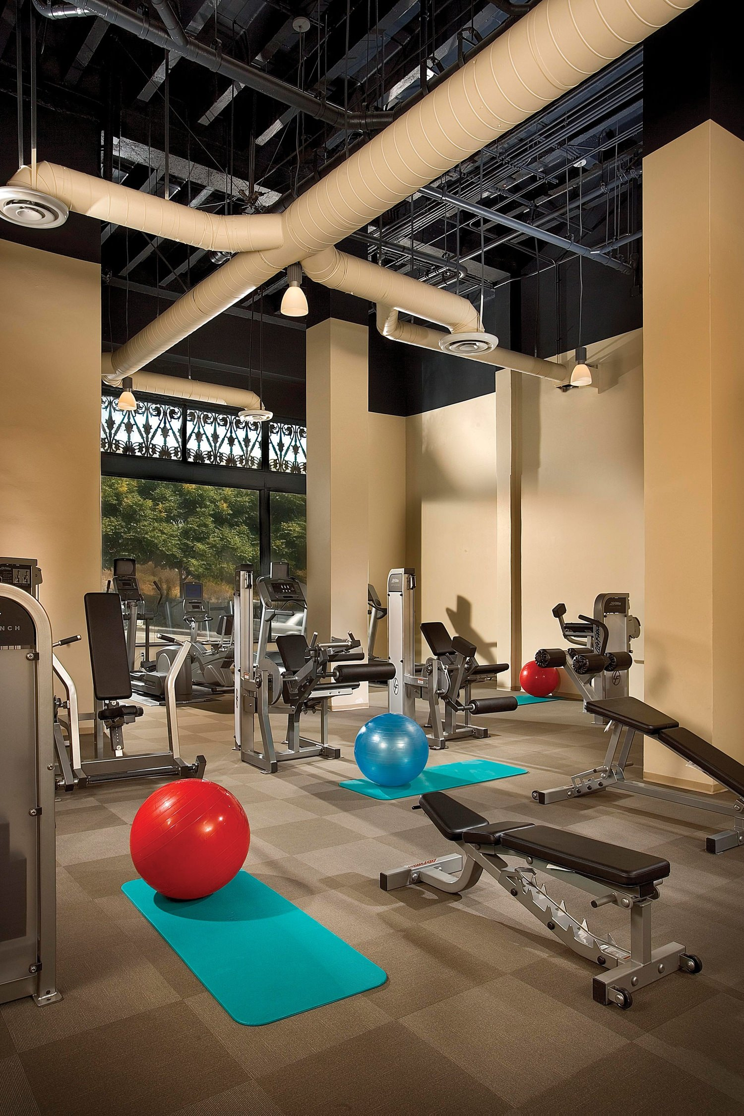A gym that is full of exercise machines and equipment along the area of the room.