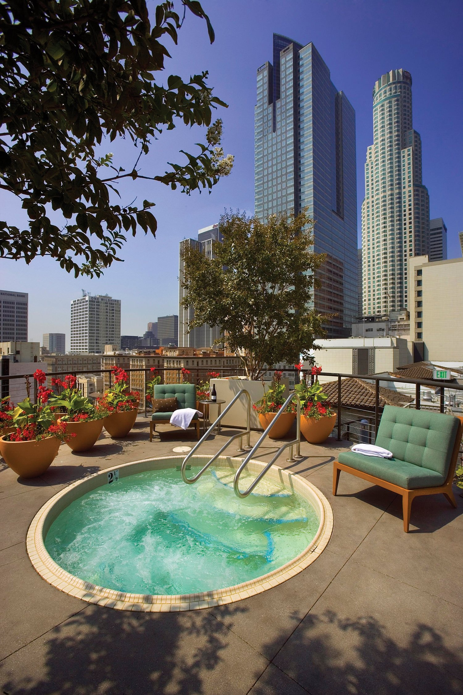 A hot tub surrounded by outdoor furniture that is at a pation of a building in the city.