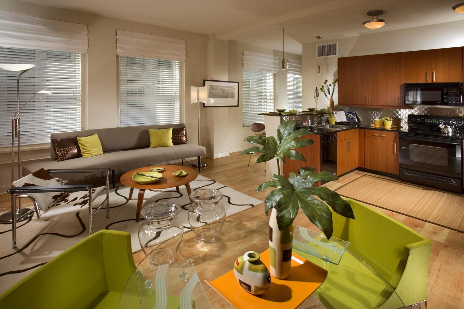 A kitchen that is next to a living room with green and grey couches along with wooden tables.
