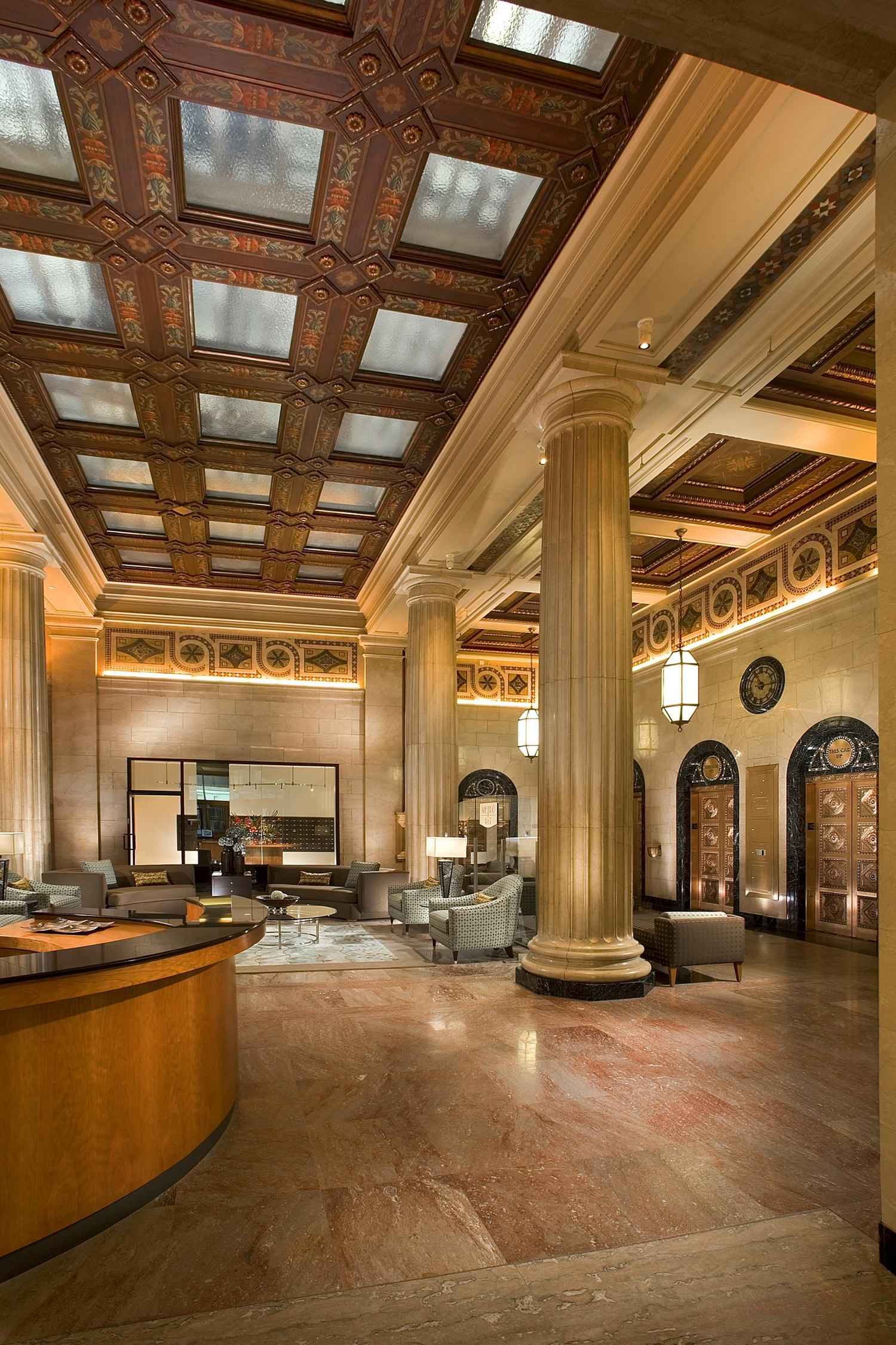 The inside of a lobby of a hotel that has some large columns in the middle of it.