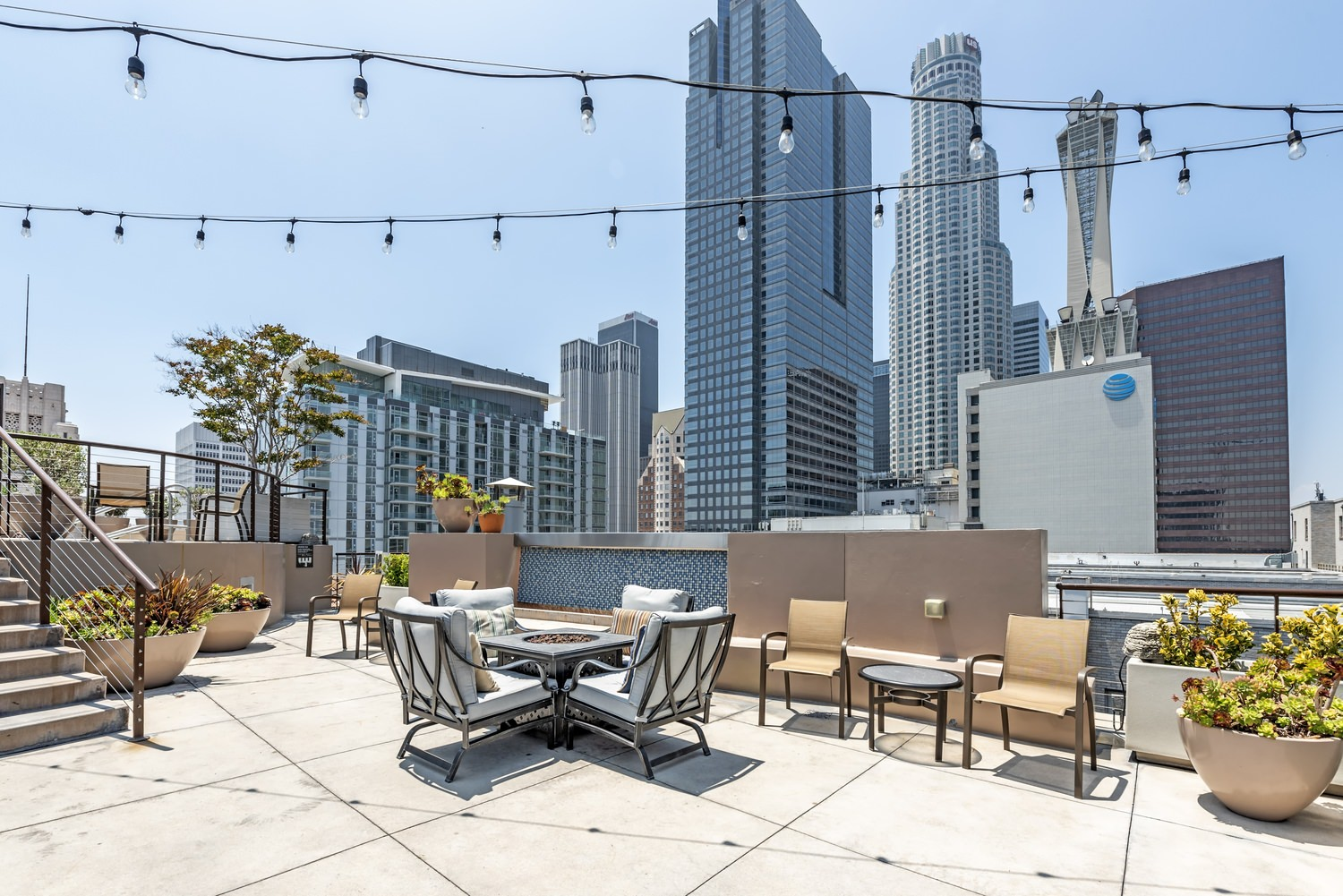 A rooftop patio that has tables and chairs as well as a fire pit, there are also planters with flowers in them.