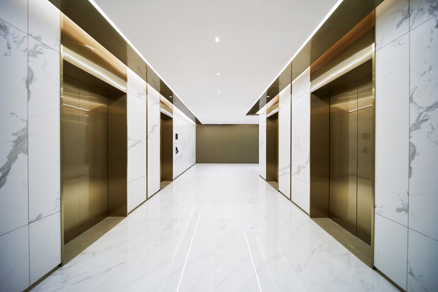 One EaThe inside of a building that has a hallway with elevators on either side of it and tile floors.st – Tower C