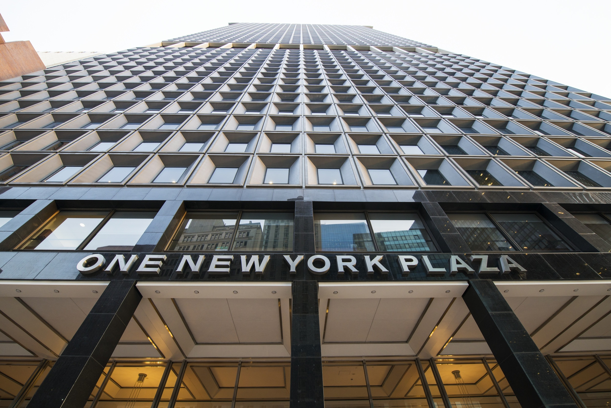 This is one new york plaza that is a tall building with a lot of windows on the face of it.